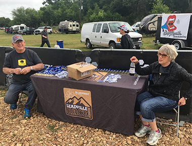 Josh's parents Larry and Chris Colley prepare to distribute finisher medals at the Austin Rattler MTB.
