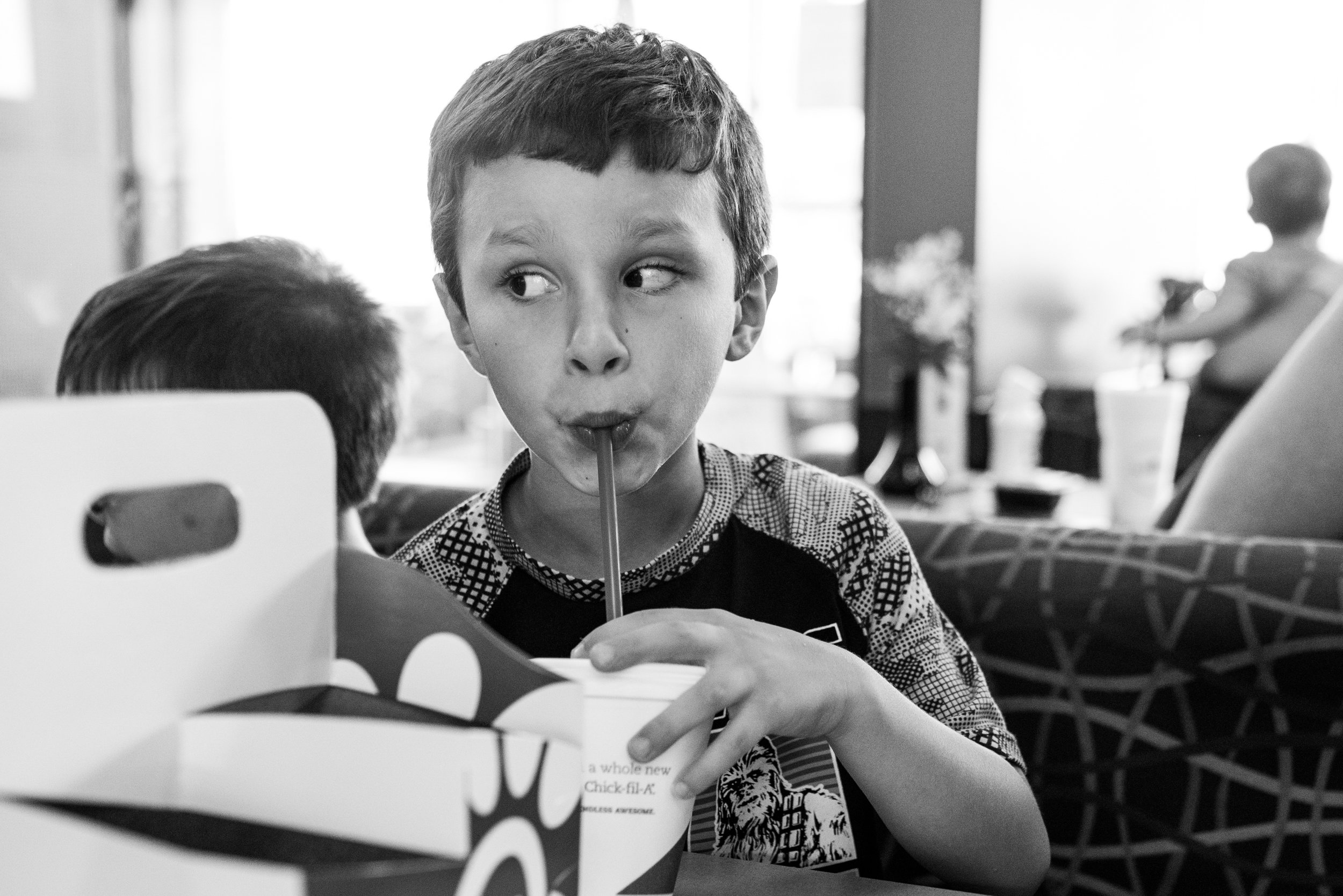 Boy drinking out of a straw sitting at a table at Chick-Fil-A in Brookfield, WI