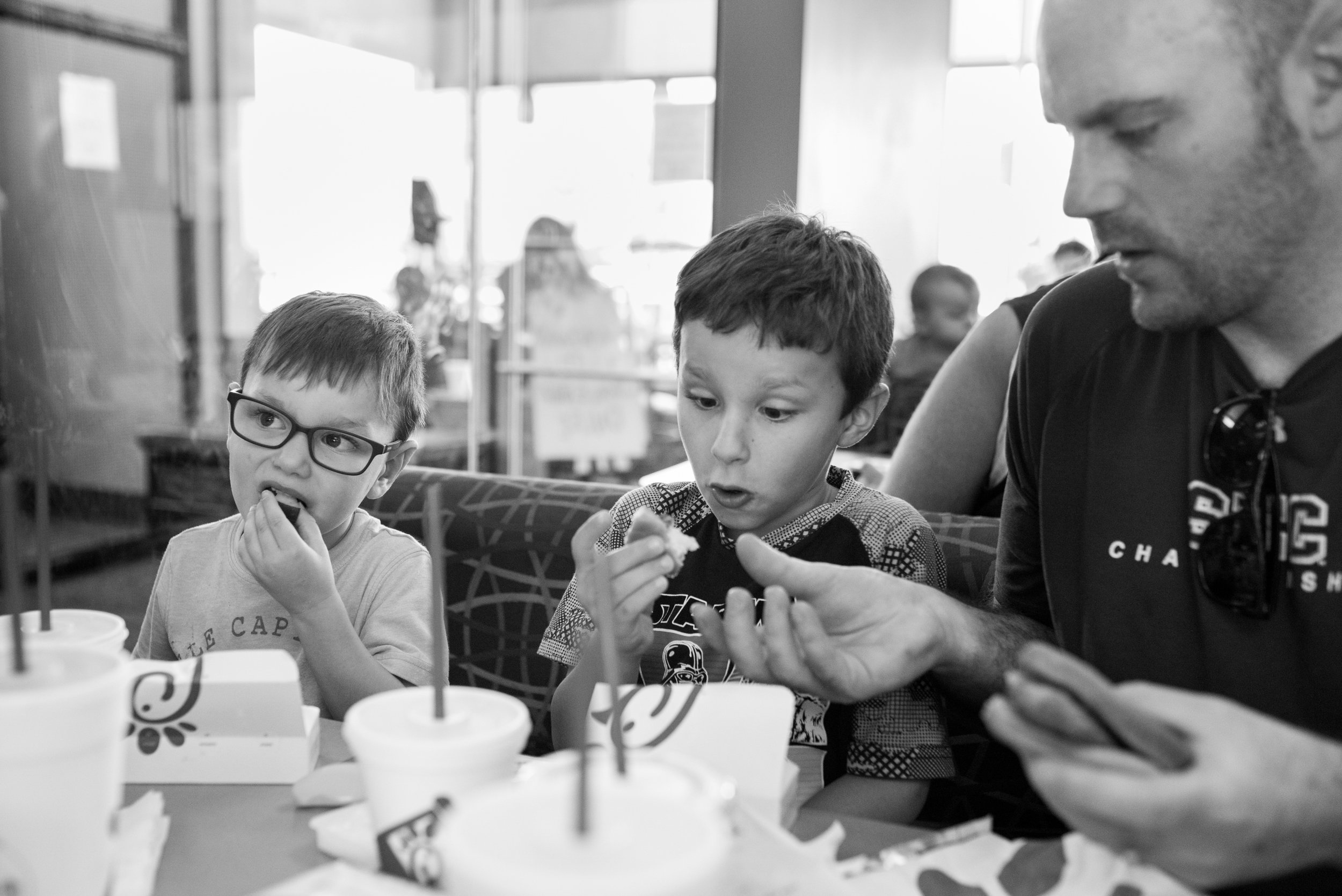 Dad handing son food at table at Chick-Fil-A while other son is eating