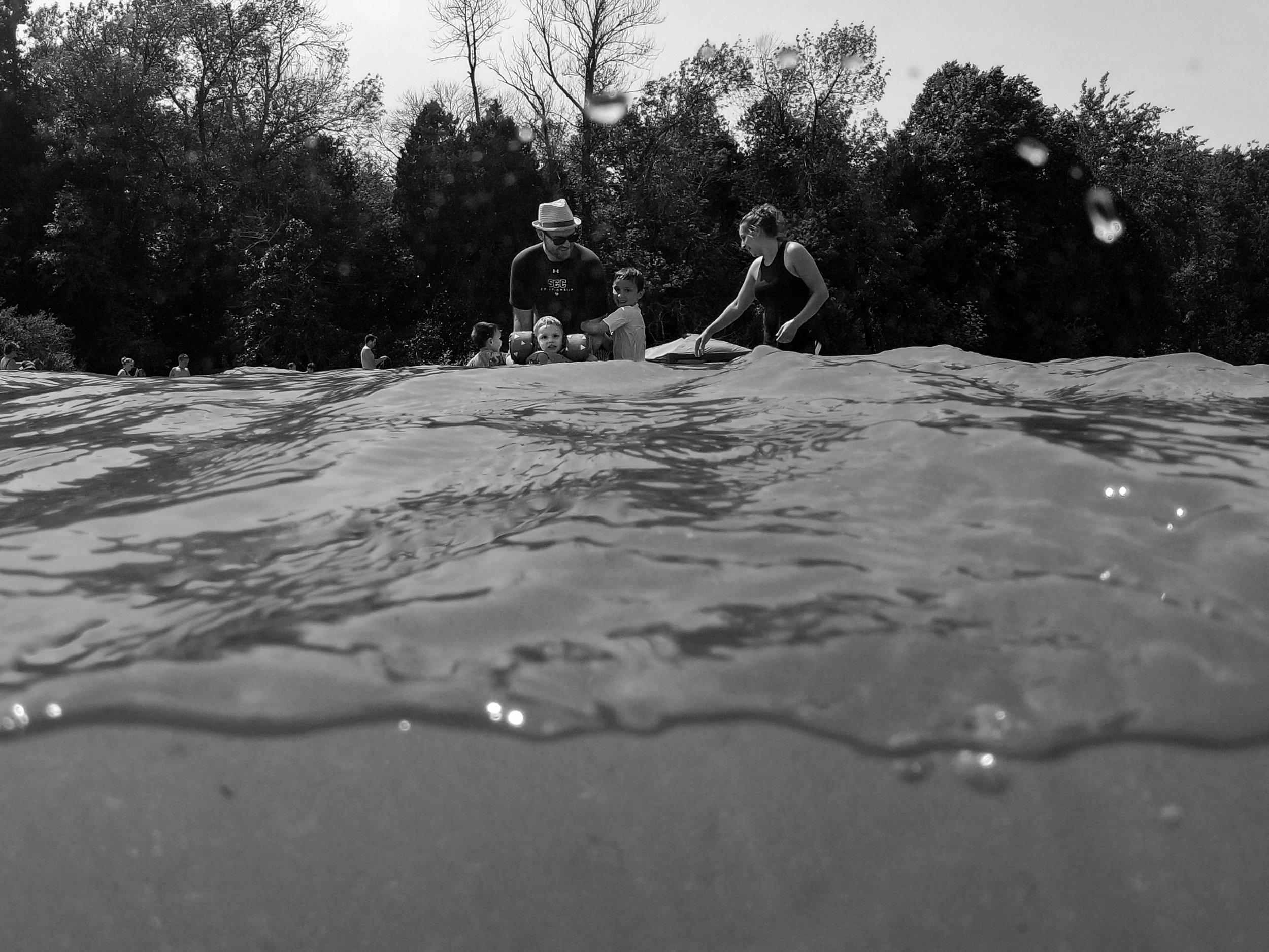 Family of 5 playing in the water, half above water half under water photo