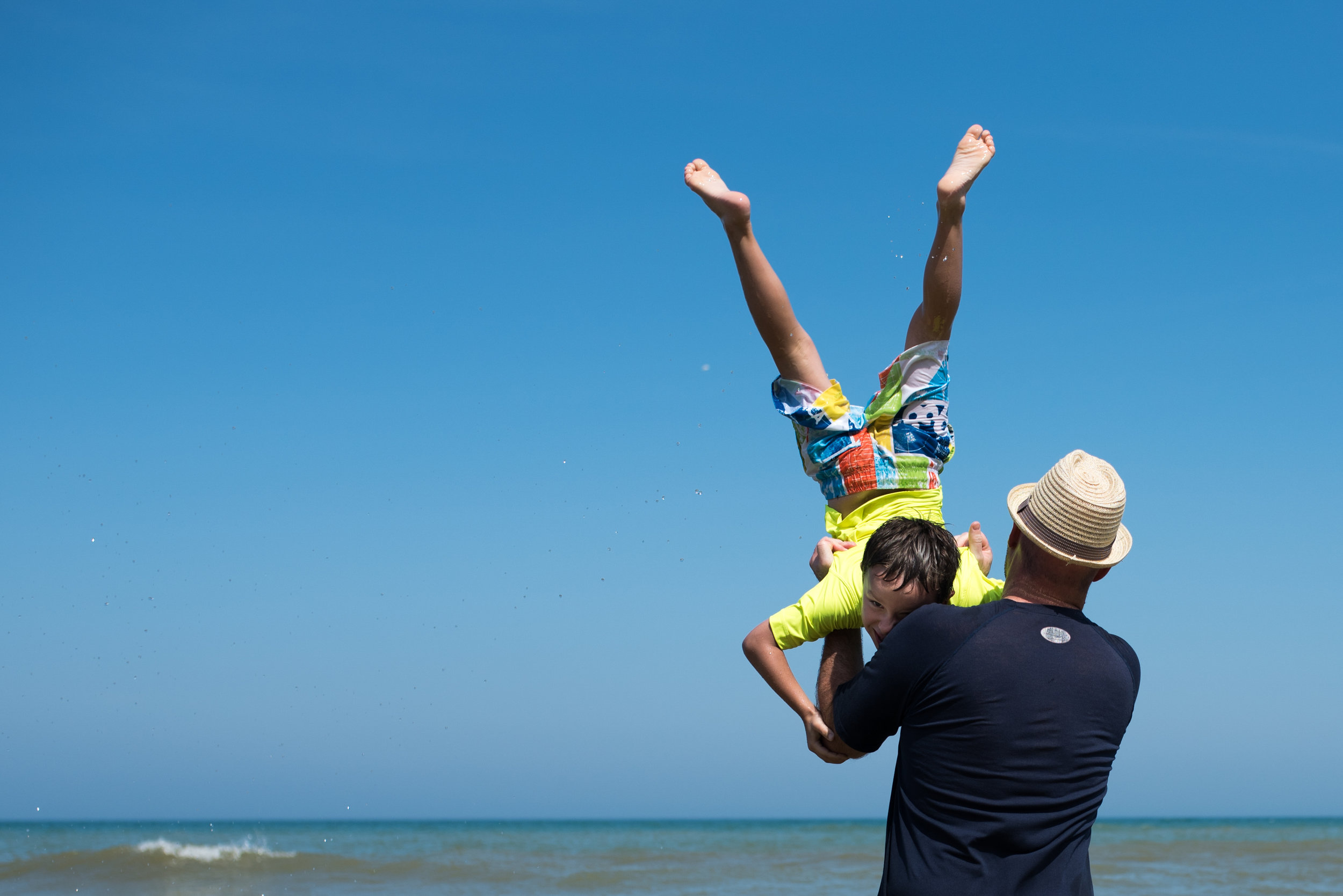 Dad swinging son straight in the air in the water, son laughing