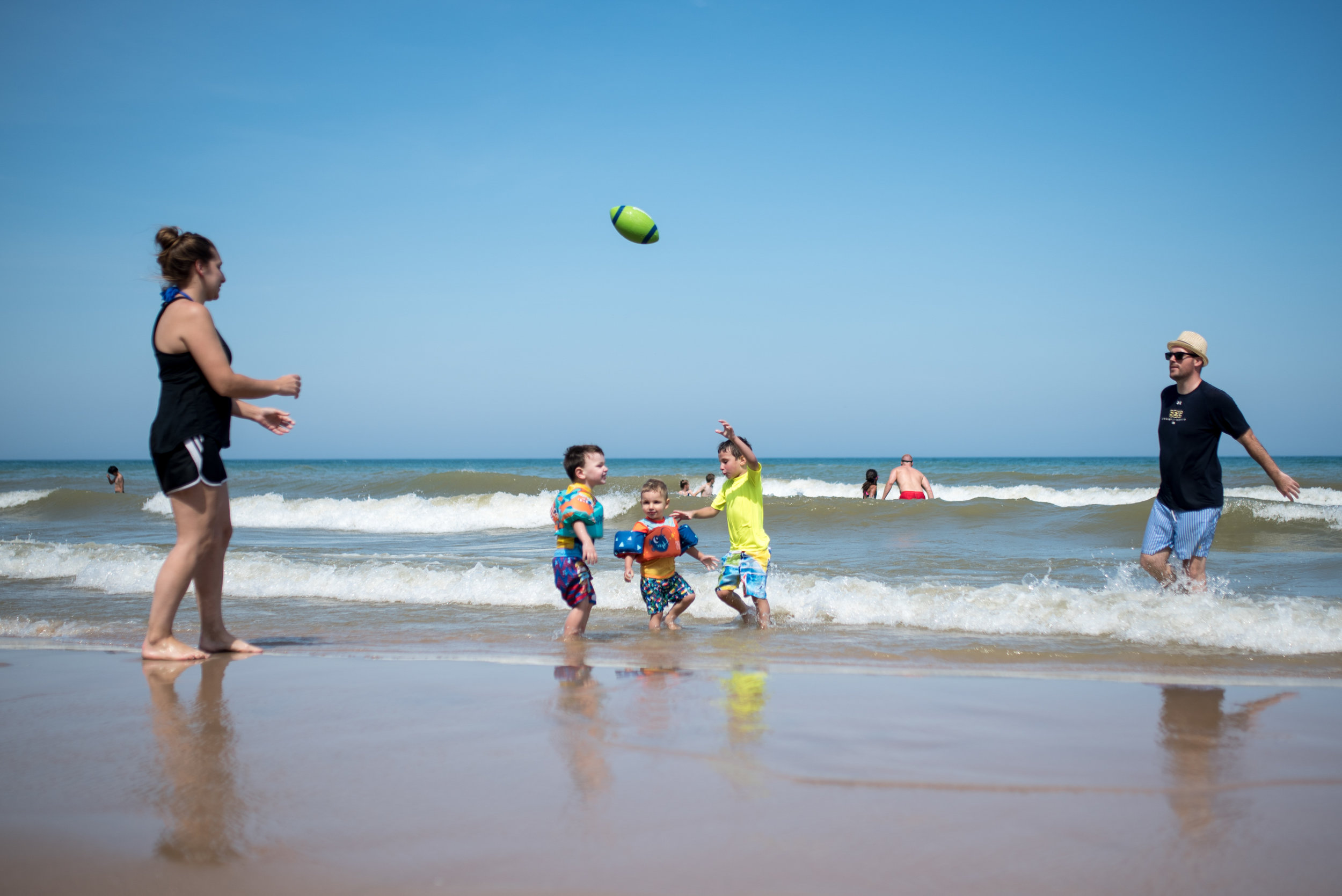 Family of 5 playing football at Harrington State Beach park. Three boys in the middle