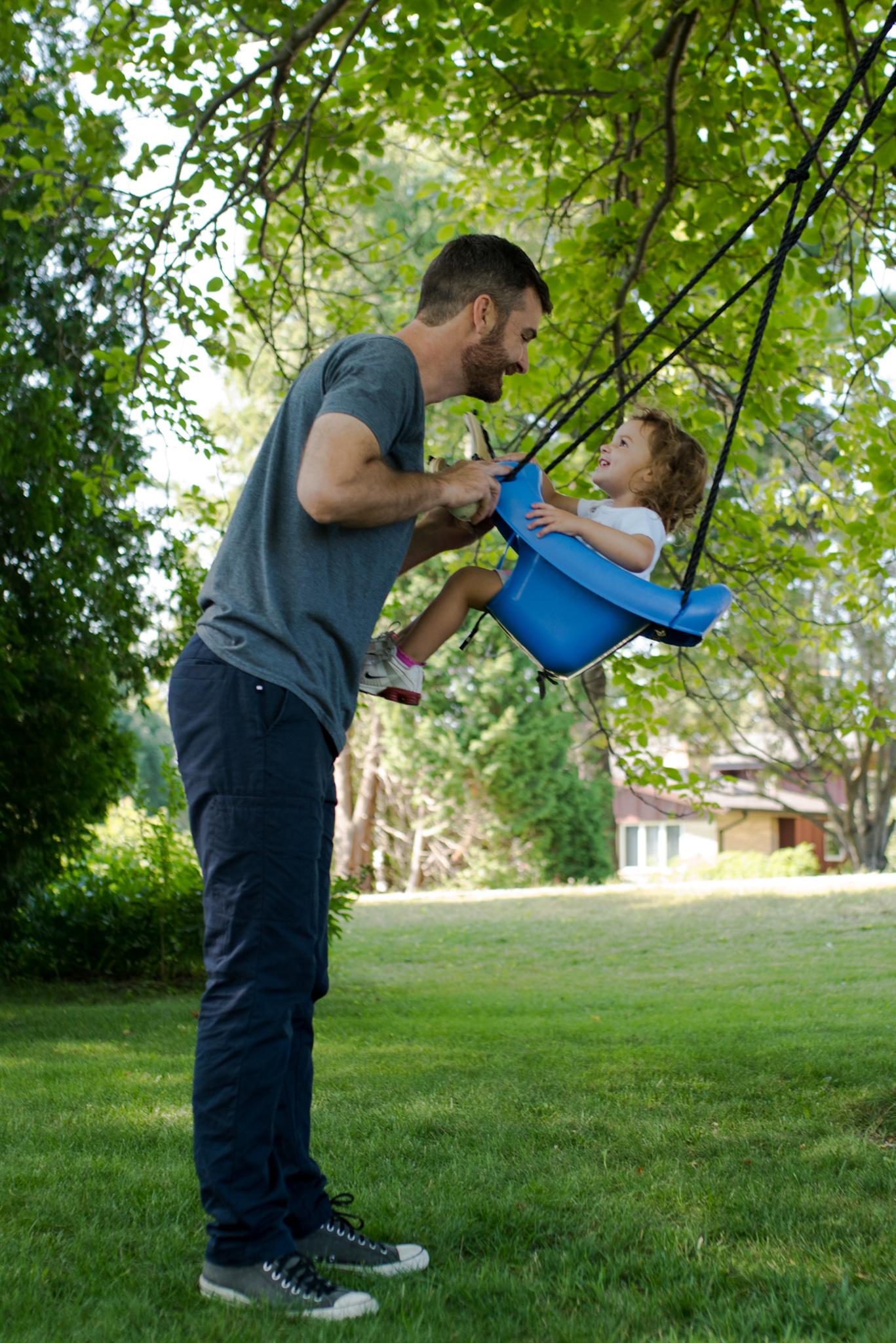 dad smiling at daughter in swing