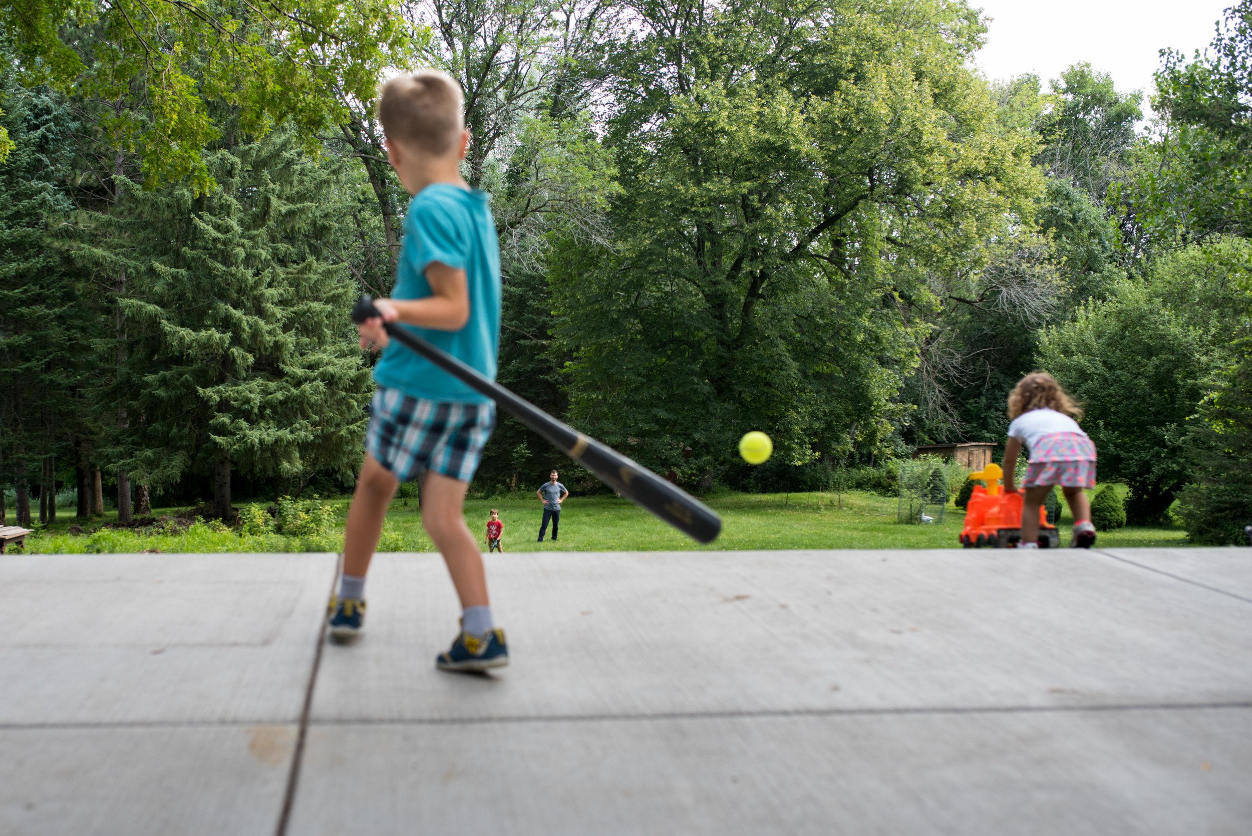 boy hitting baseball in yard with family