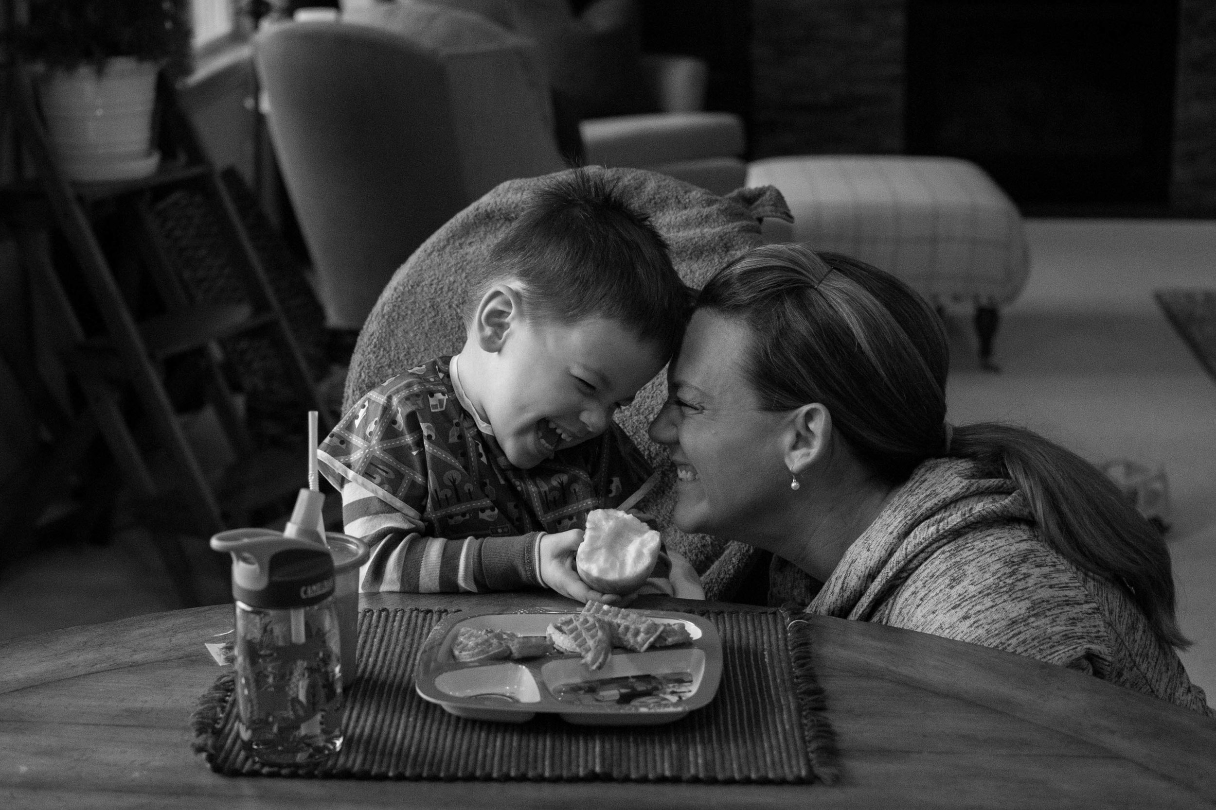 Mom and son smiling in the kitchen during an Appleton Photography session