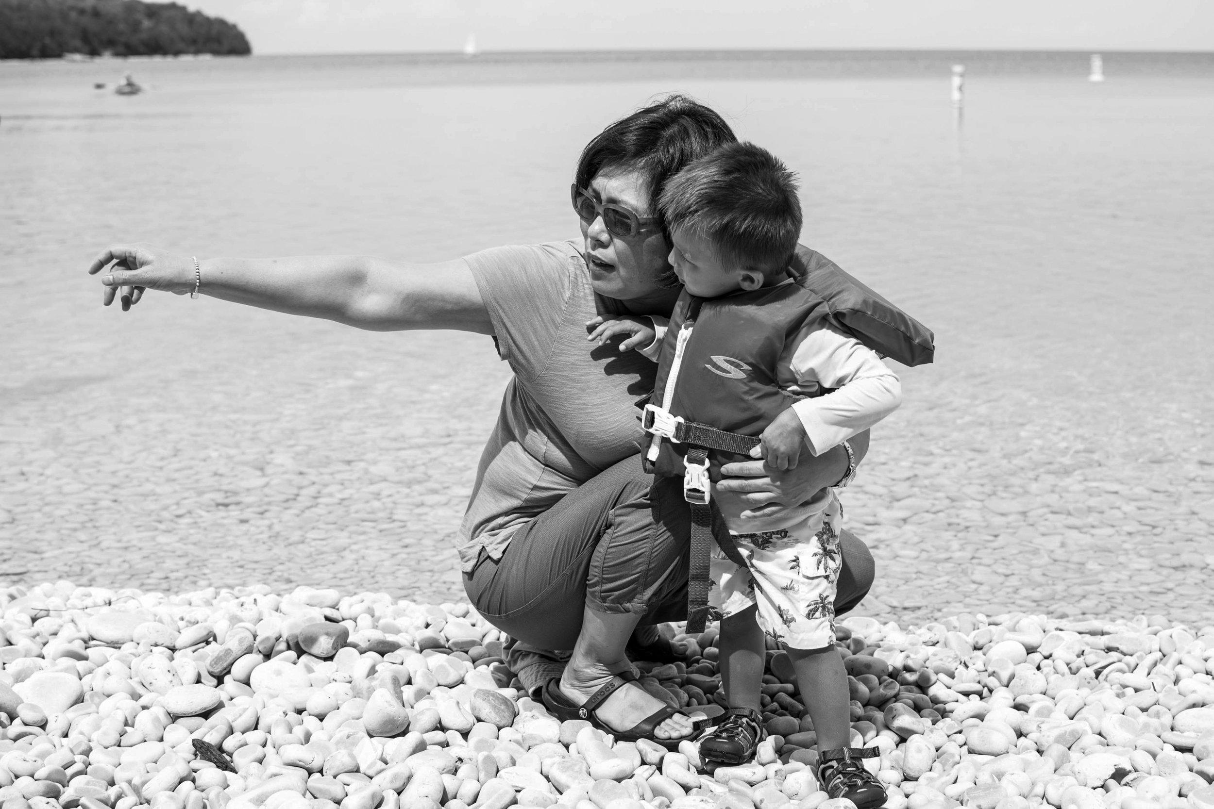 Grandma helping grandson on shore of Schoolhouse Beach, Washington island, Wisconsin