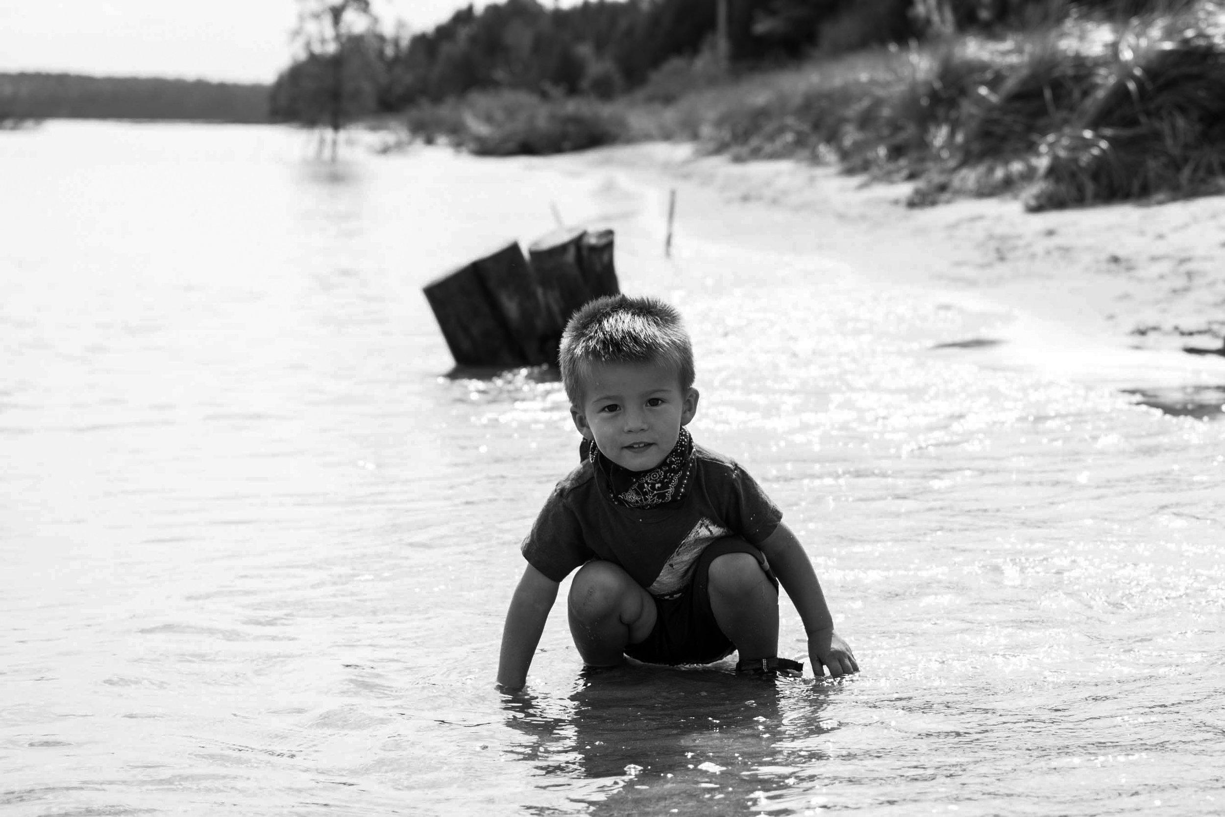Boy in water on sandy beach