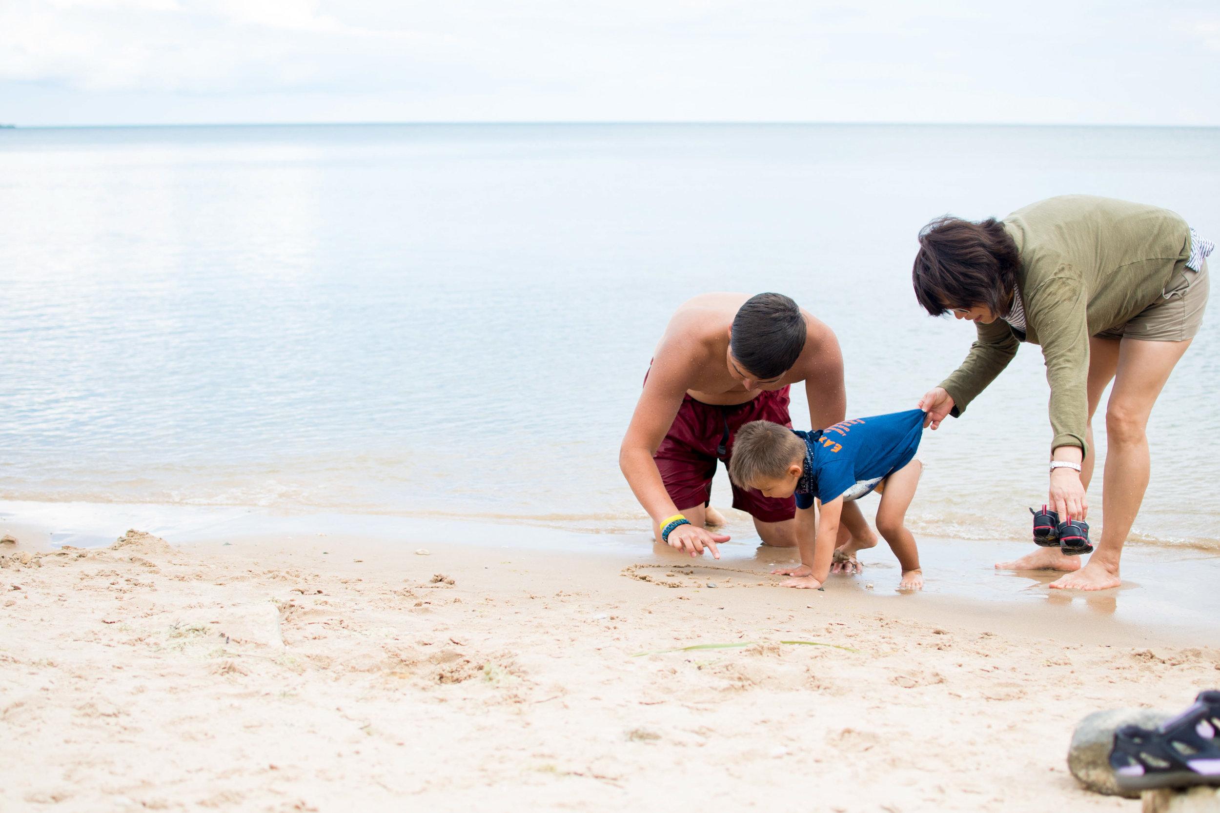 Grandma holding grandsons shirt on beach