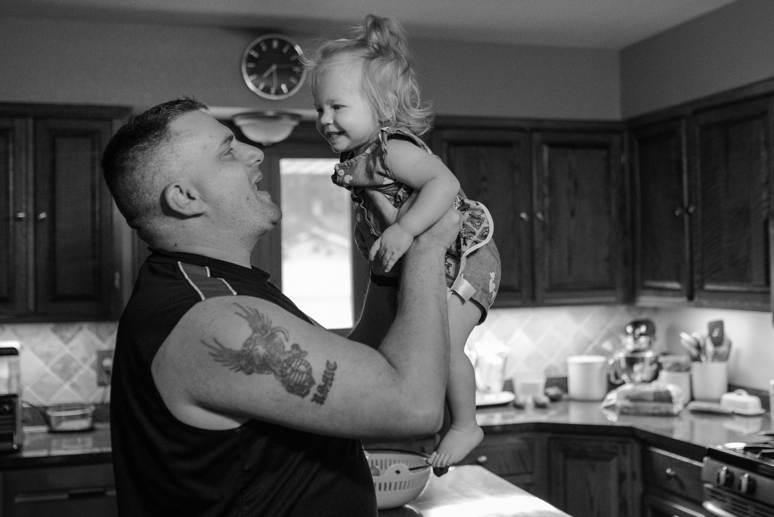 Dad holding up smiling toddler daughter in the kitchen
