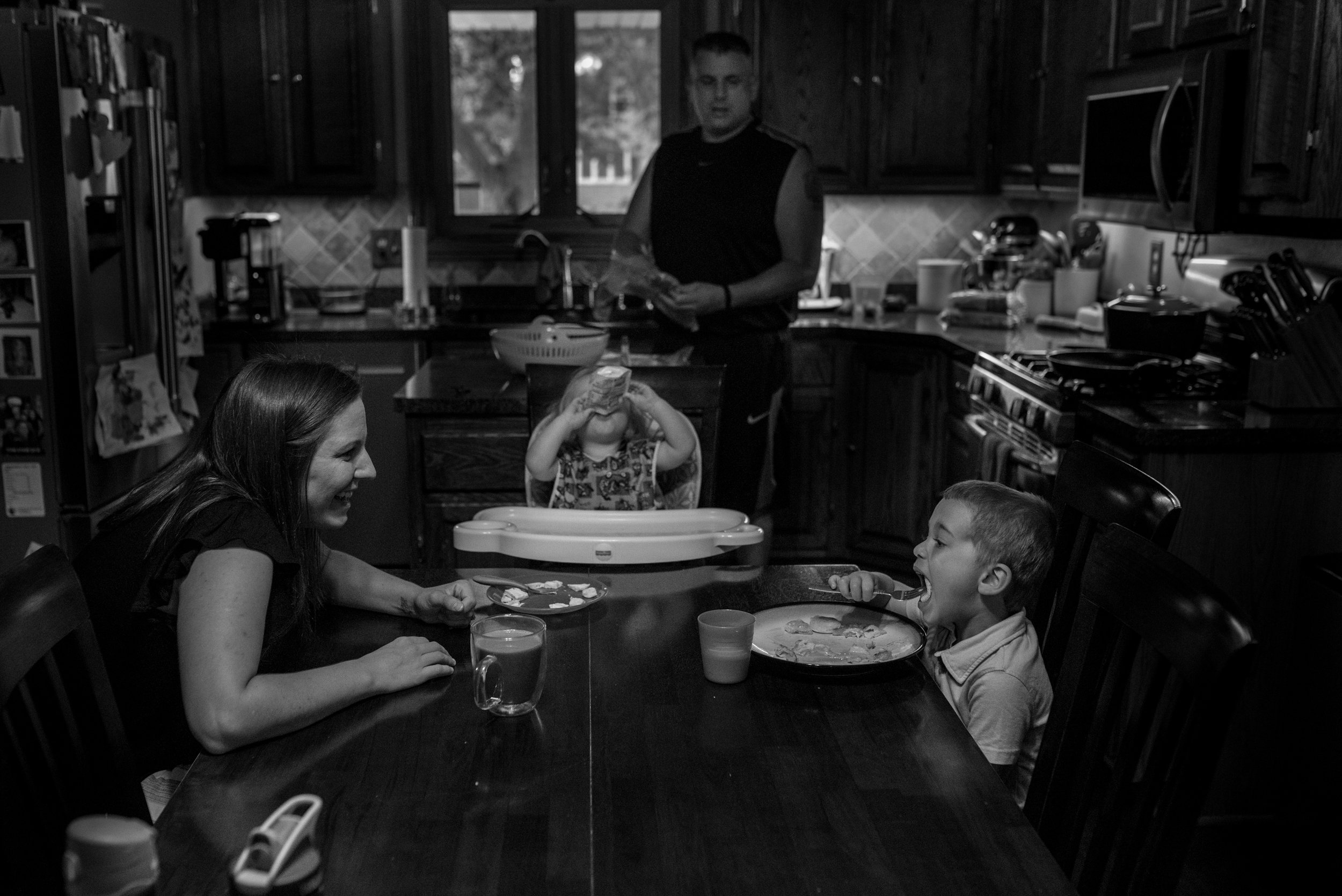 Family of four eating breakfast.  Mom smiling at son eating eggs, daughter eating a pouch and dad drying dishes