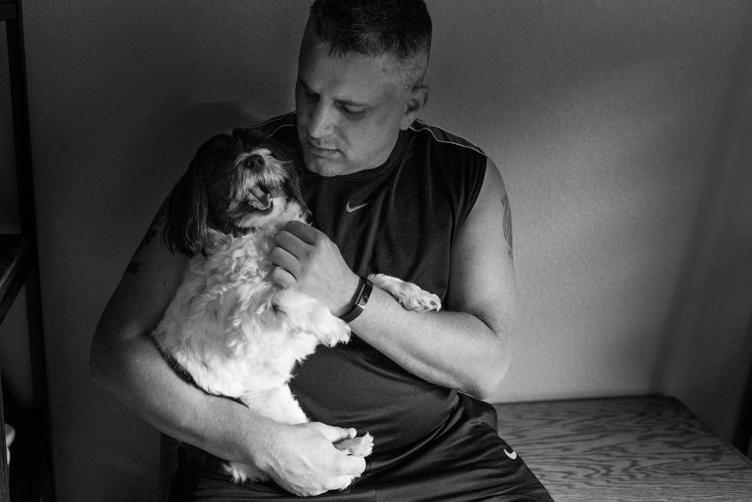 Man sitting, holding and petting small black and white dog