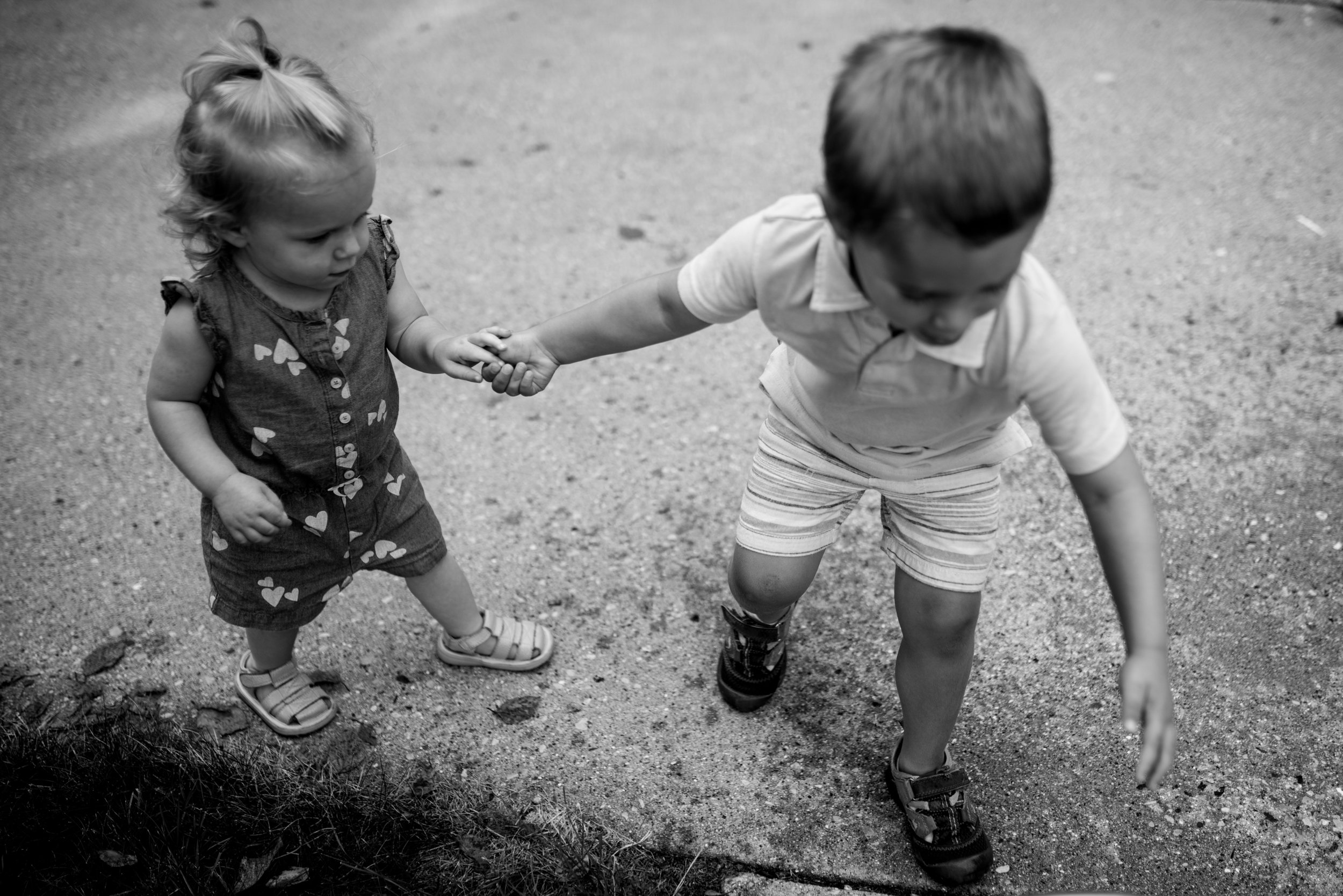 Brother holding sisters hand and leading her on the driveway during a West Bend family in home session