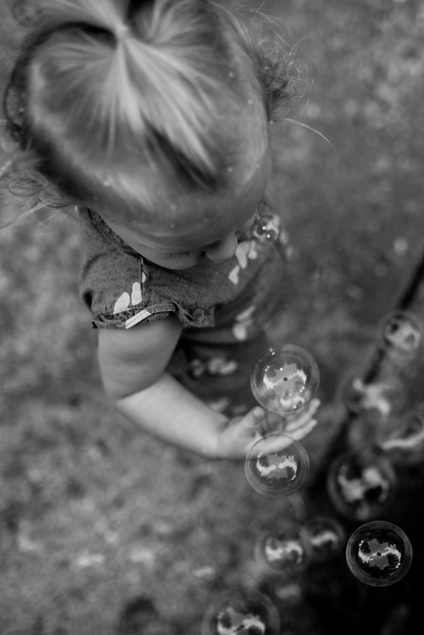 Toddler girl playing with bubbles almost holding one in her hand