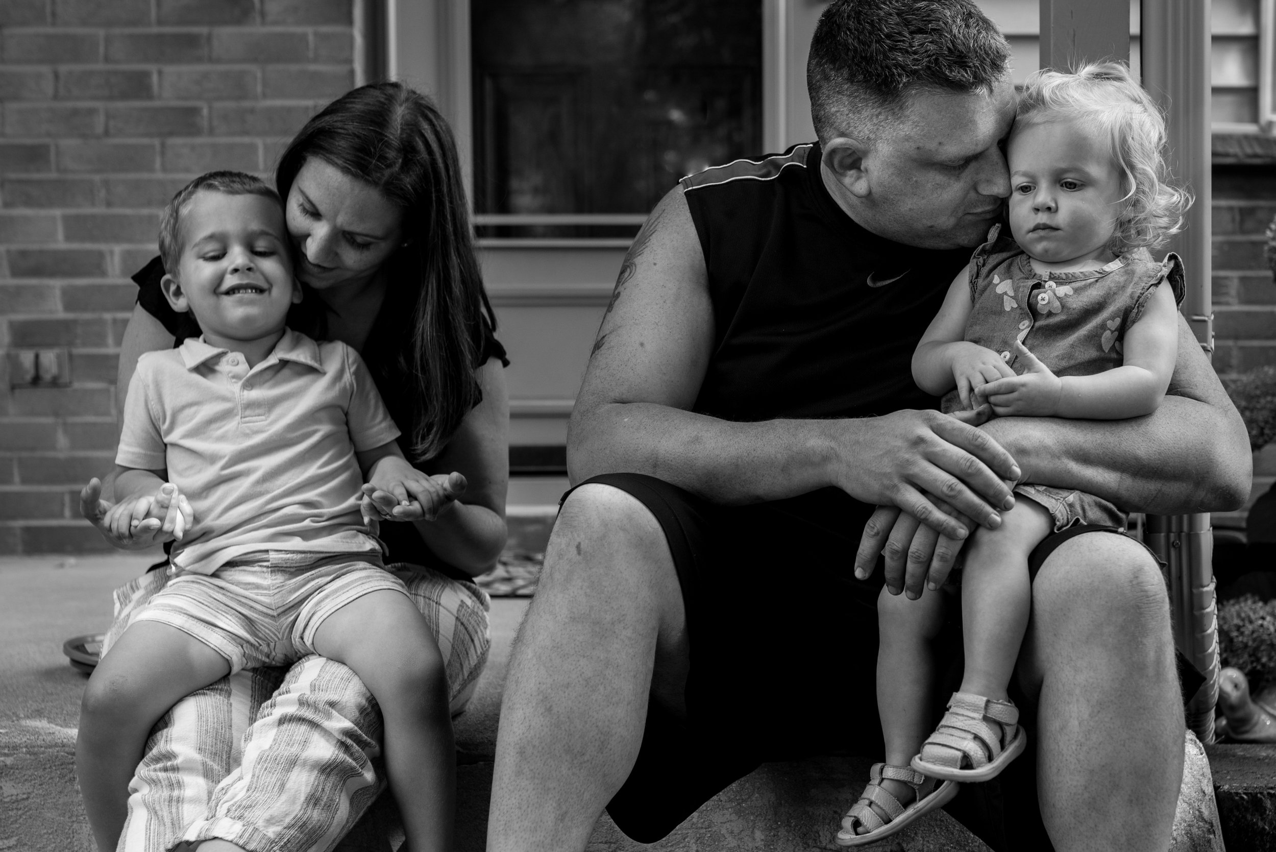 Family of four sitting on front porch. Mom, dad, son and toddler daughter snuggling during West Bend Family In home session