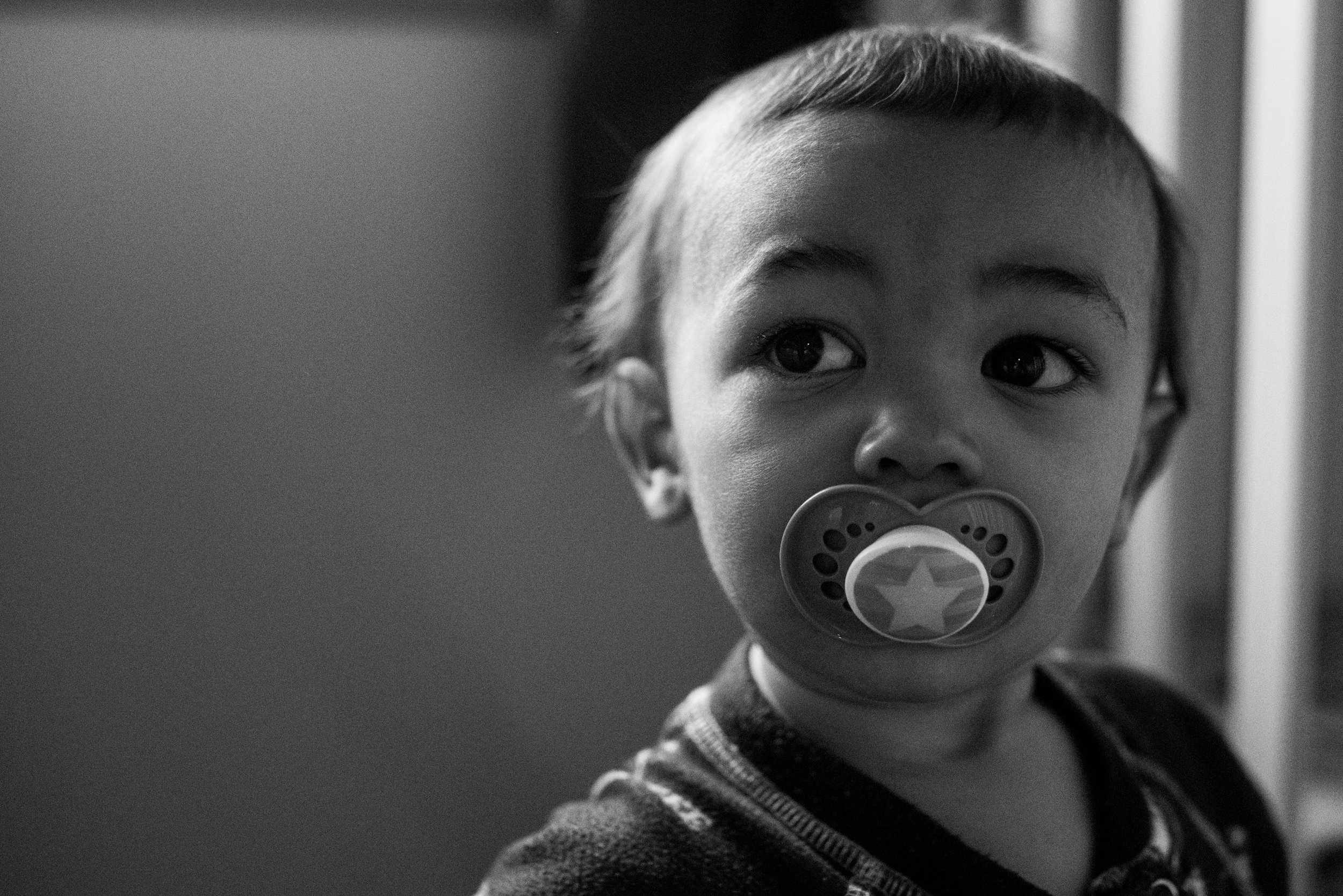 Toddler boy with pacifier in his mouth