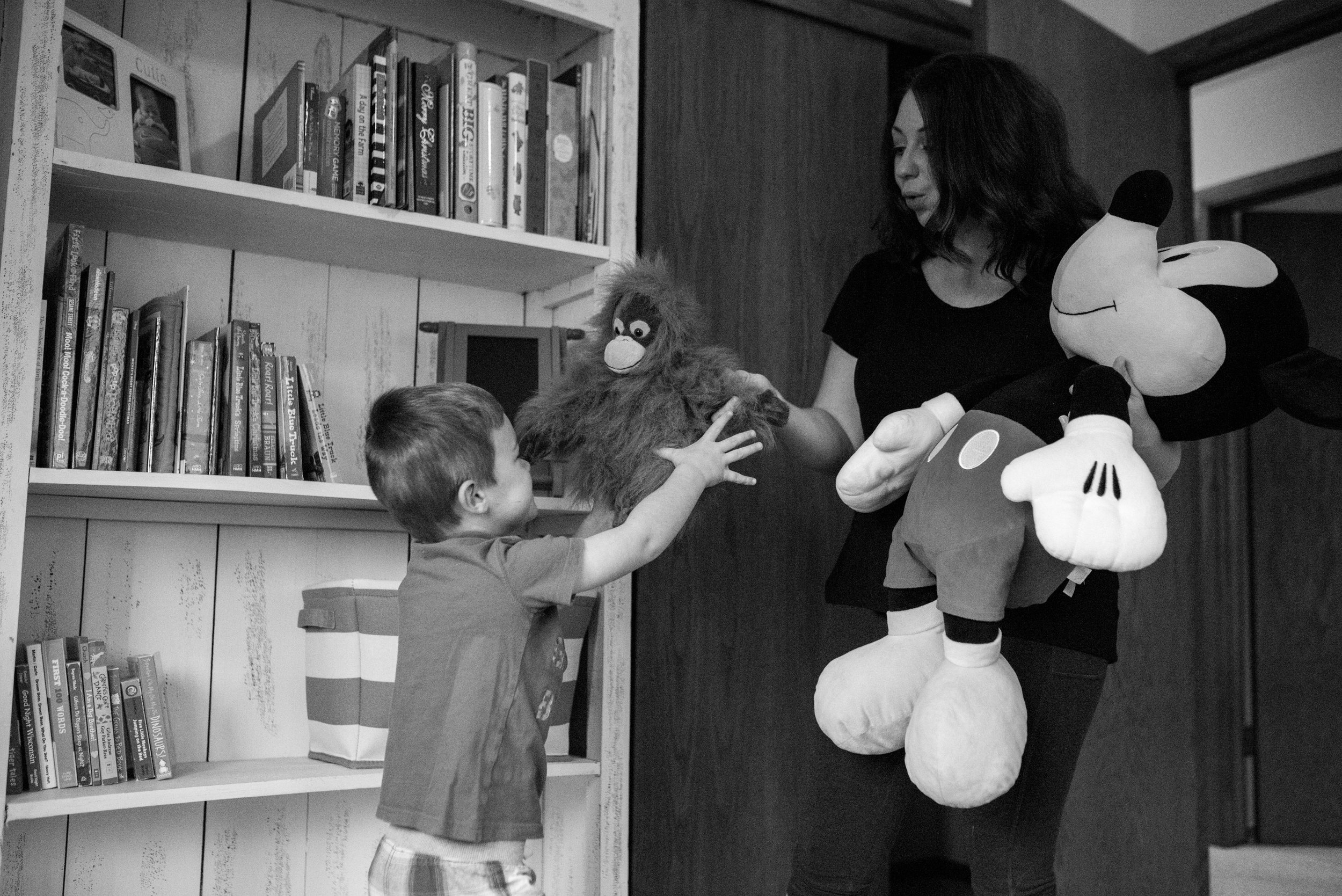 Mom handing son gorilla stuffed animal and holding Mickey Mouse stuffed animal