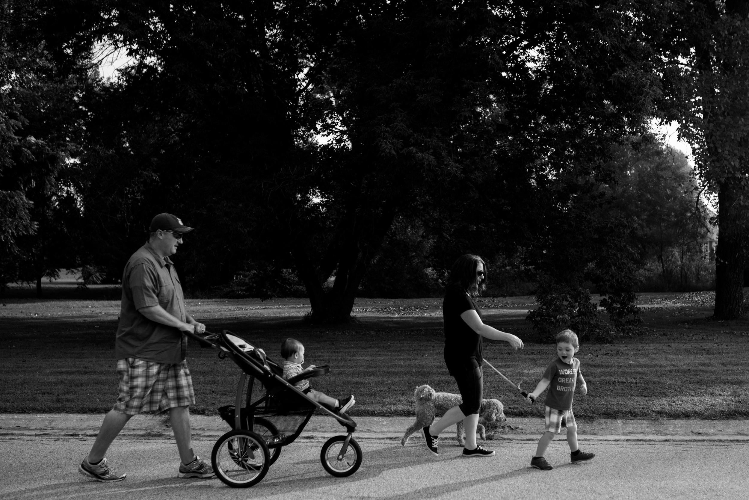 Family walking down the road. Dad pushing stroller with toddler boy, mom and son walking dog