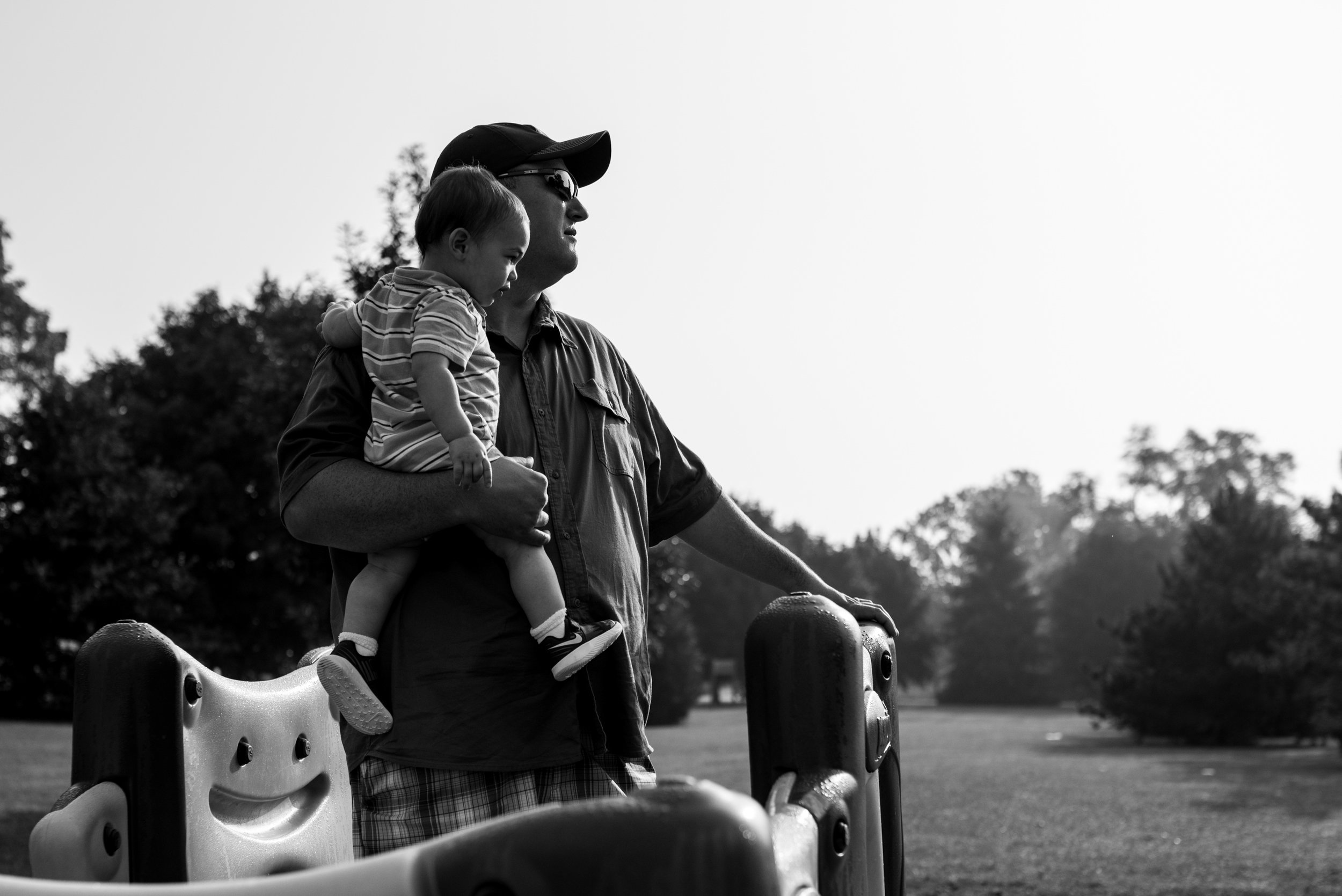 Dad holding toddler son on playground at park looking into the distance