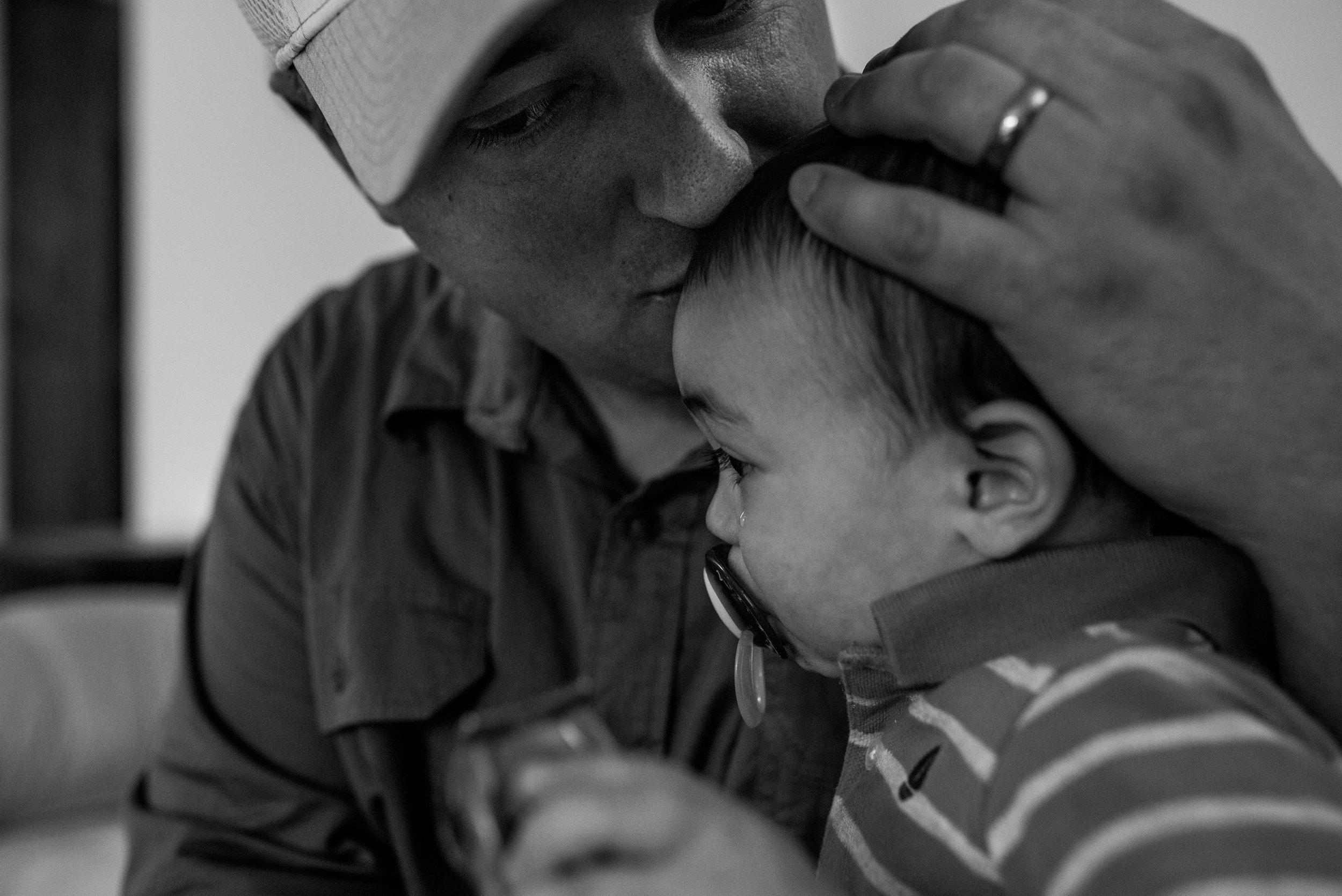 Dad kissing crying toddler son on the forehead during a muskego family photography session
