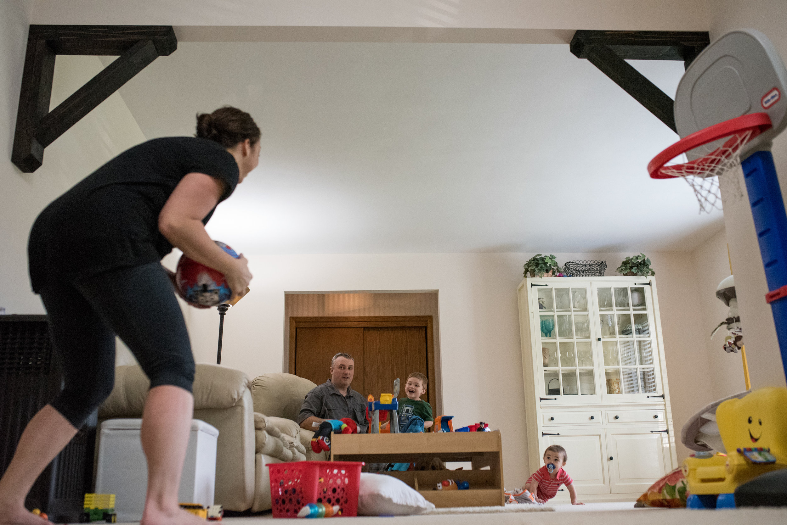 Mom playing basketball in living room while husband and two sons watch
