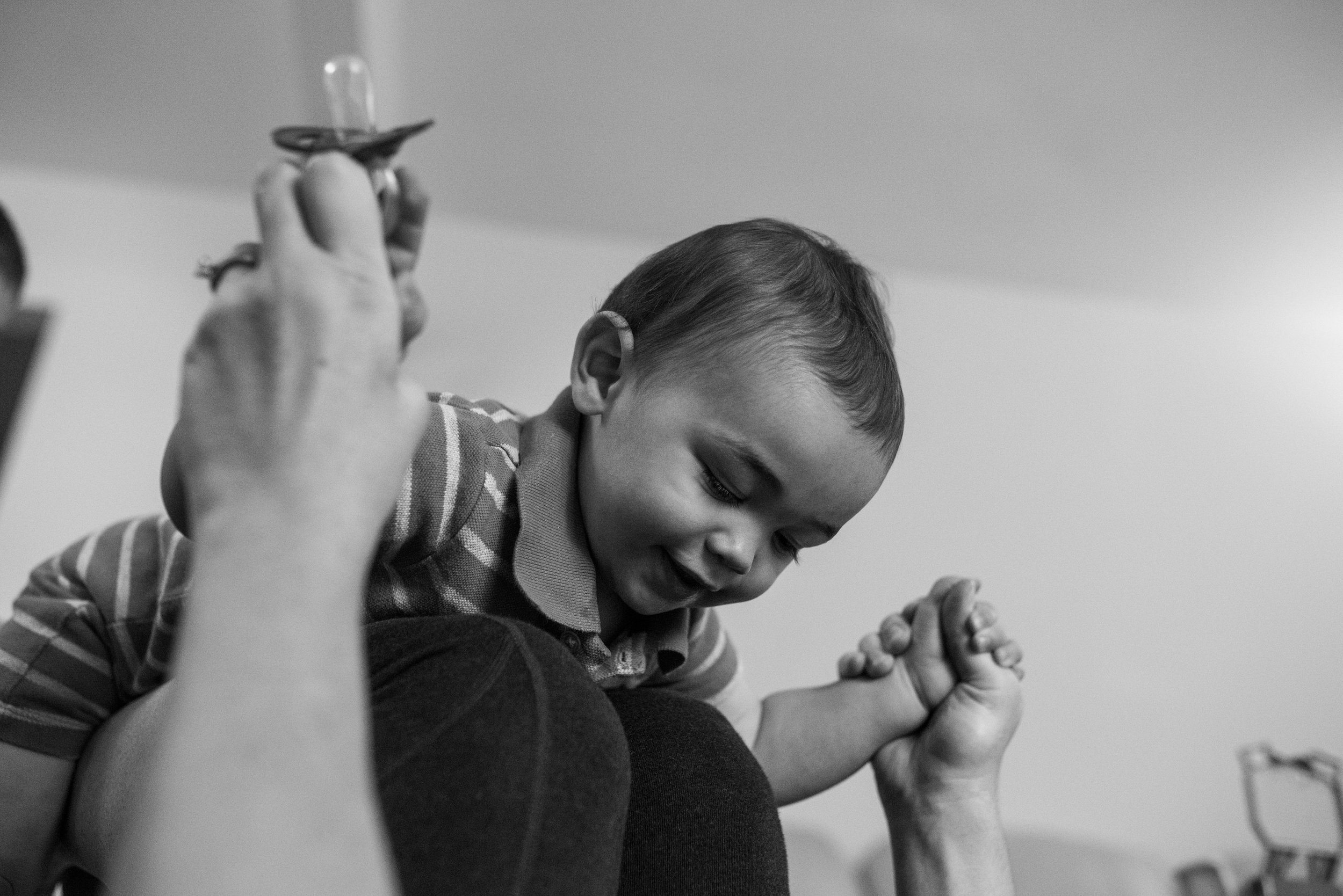 Mom balancing toddler son on her legs and pacifier in her hand