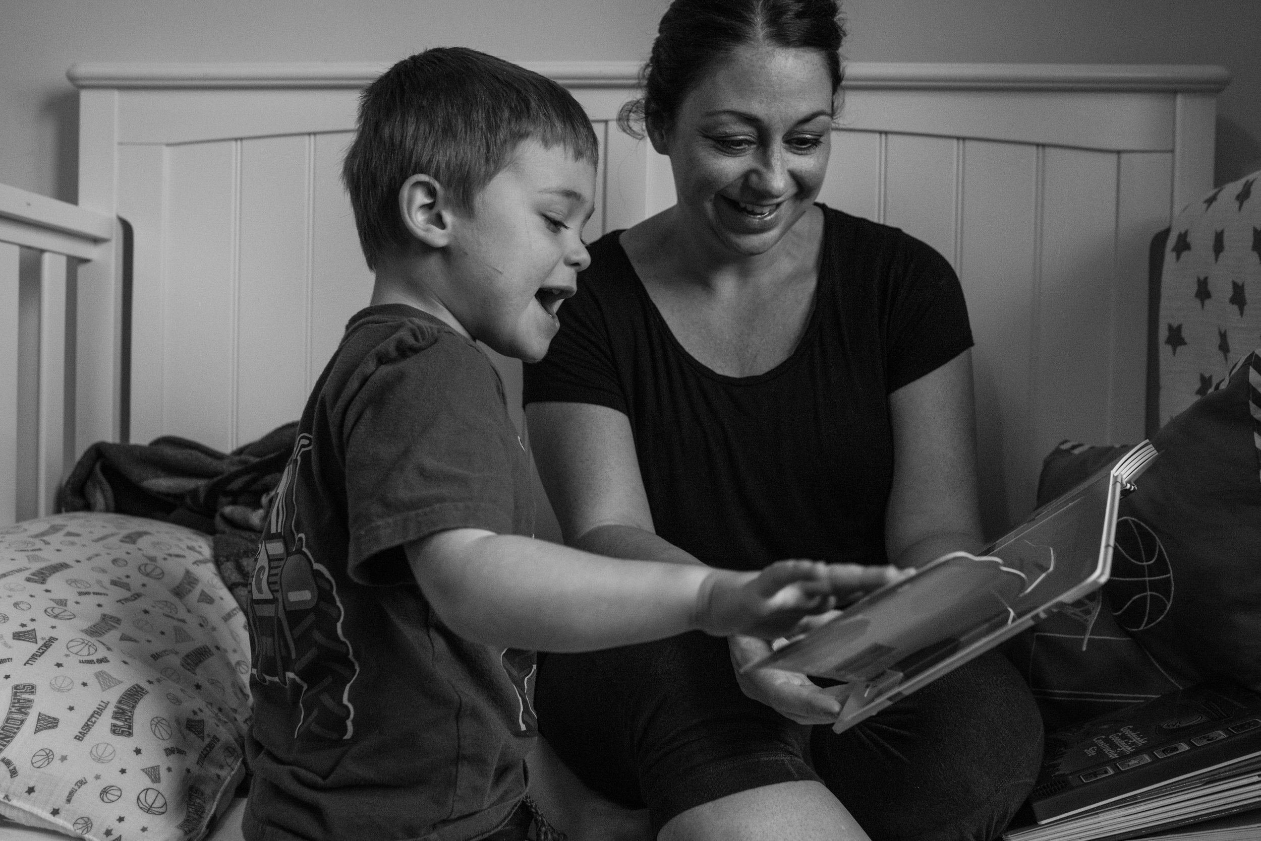 Mom and son reading a book in his room sitting on the bed