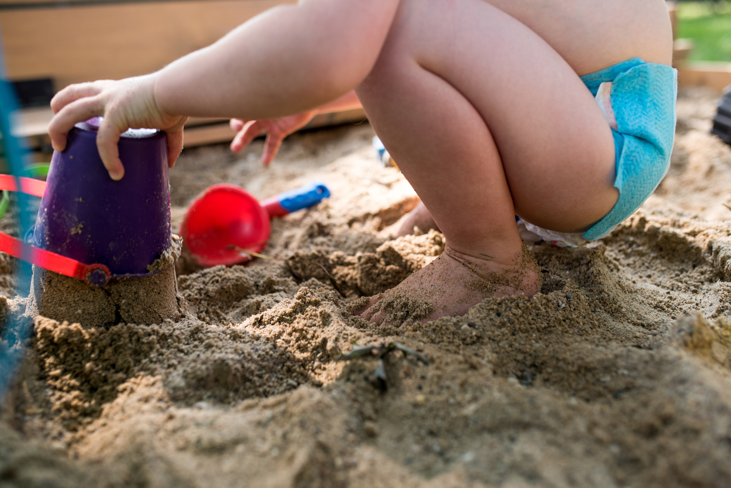 Boy playing in the sandbox with swim diaper on covered in sand
