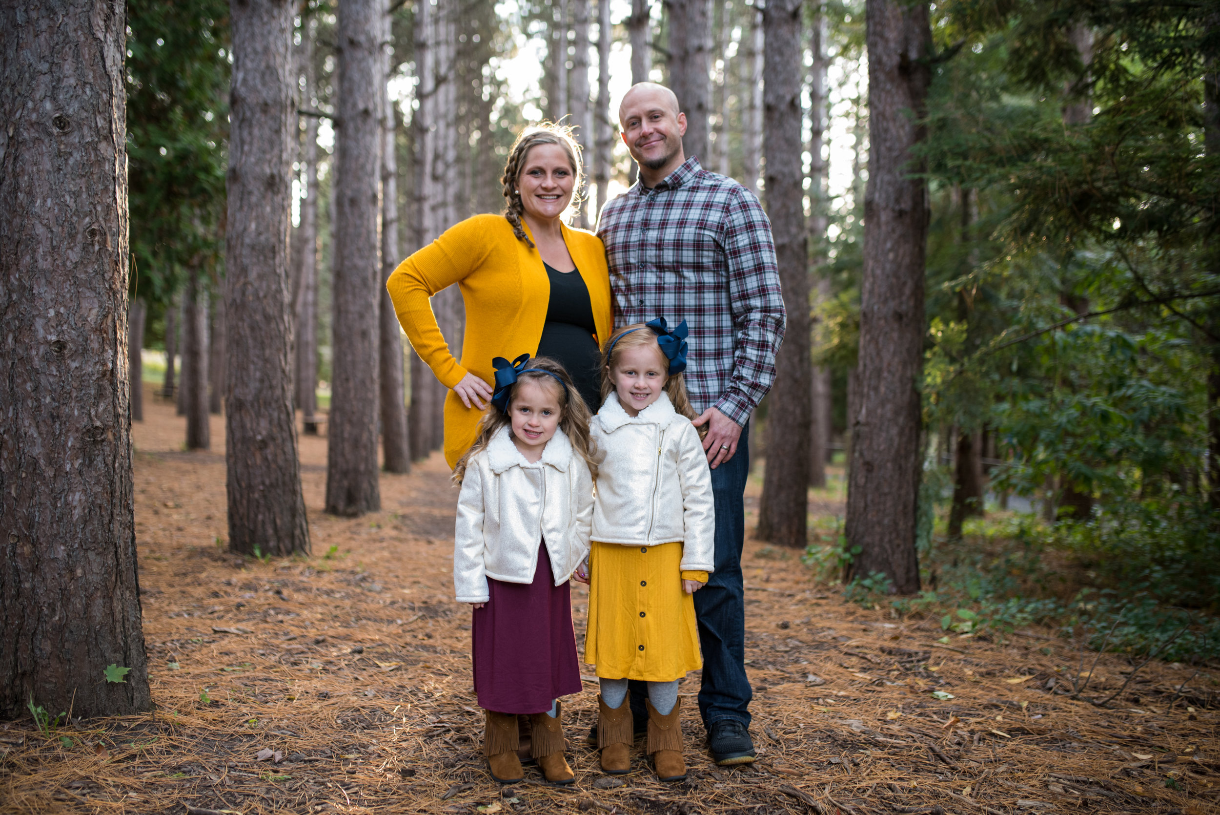 Family posing, smiling at camera in pine trees at Retzer Nature center