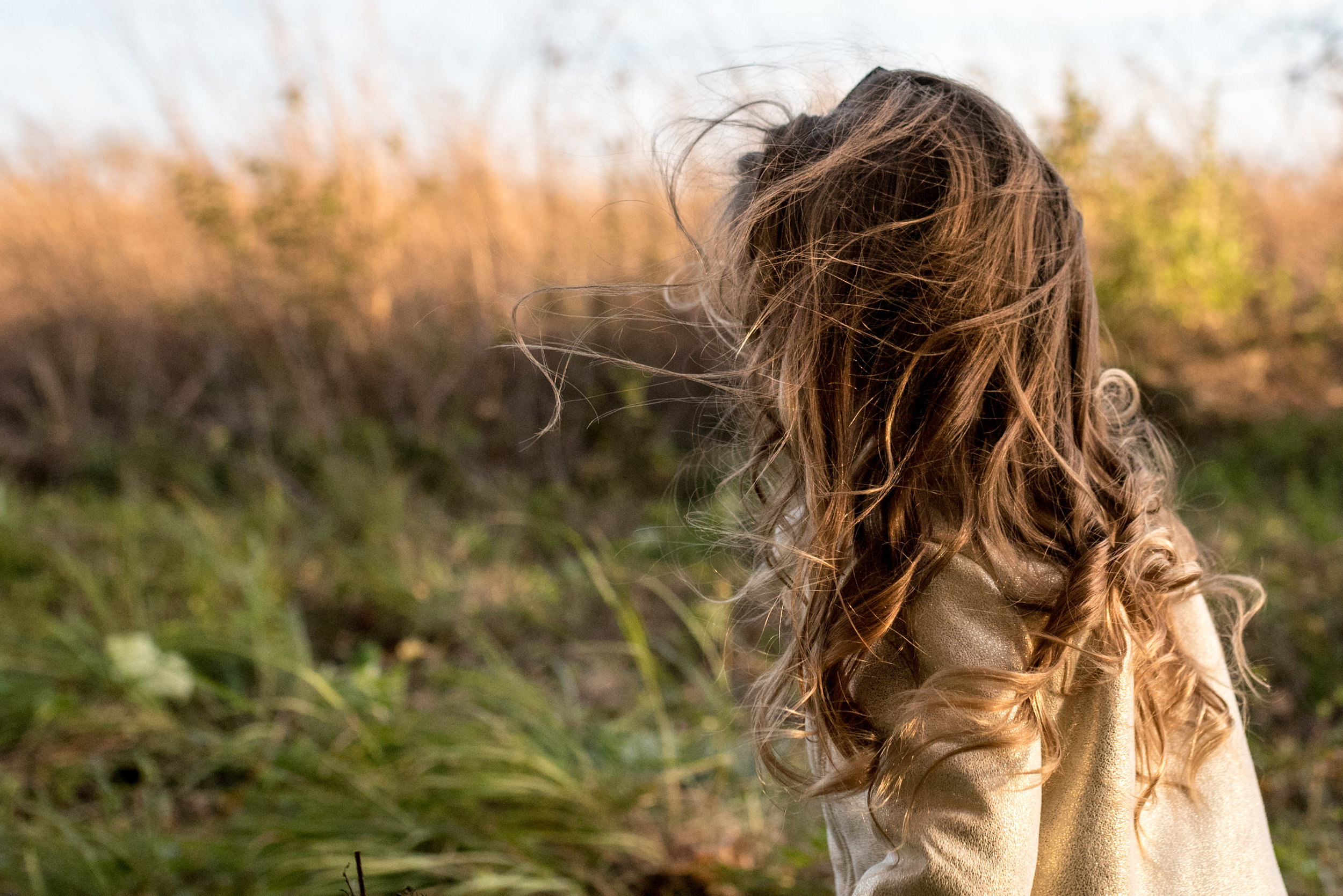 Young girl in a field with long hair blowing in the wind