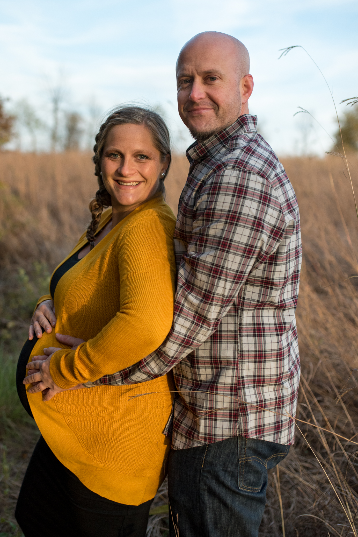 Dad holding mom and her pregnant belly in a field smiling