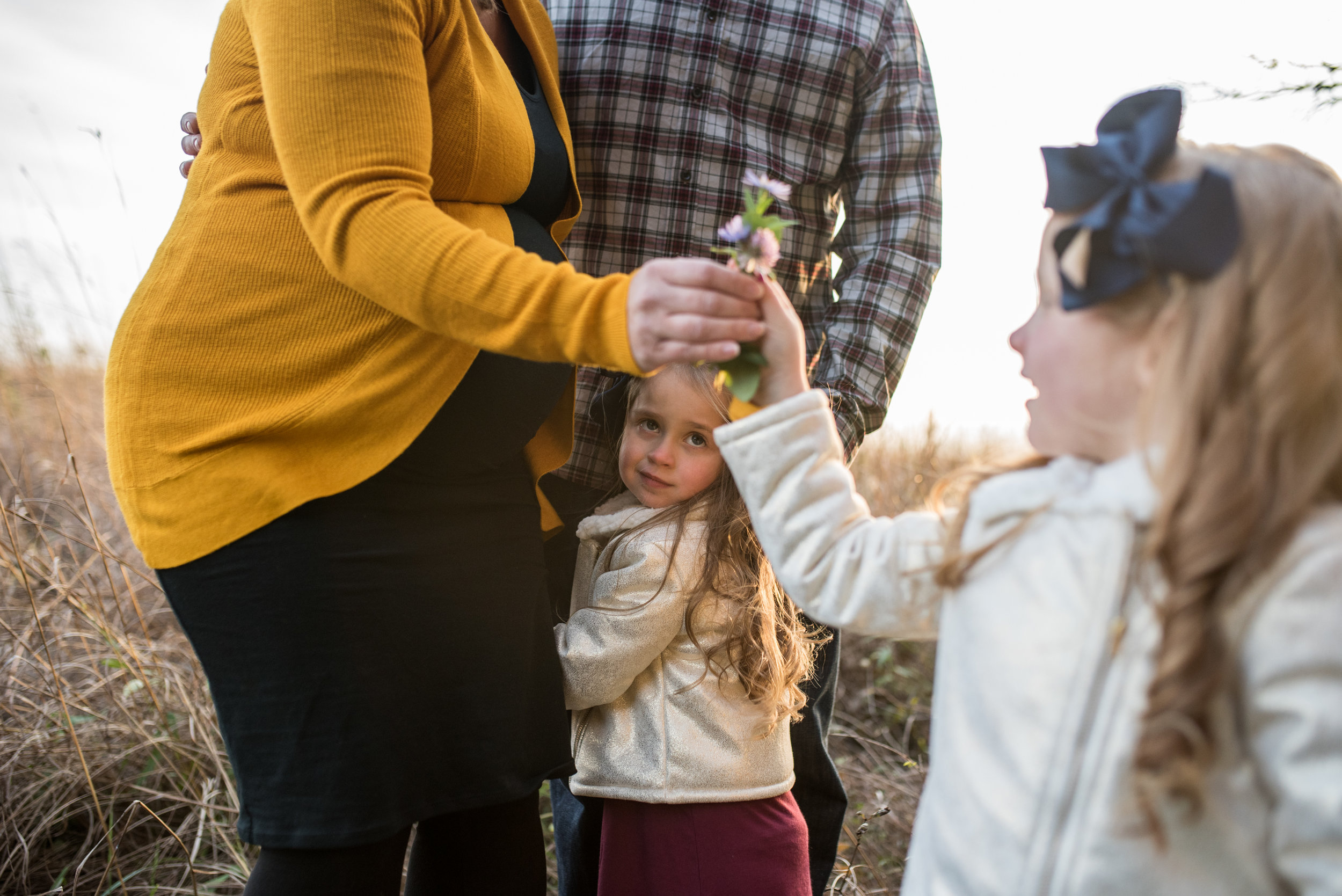 Daughter hugging moms legs, another daughter handing wildflowers to mom