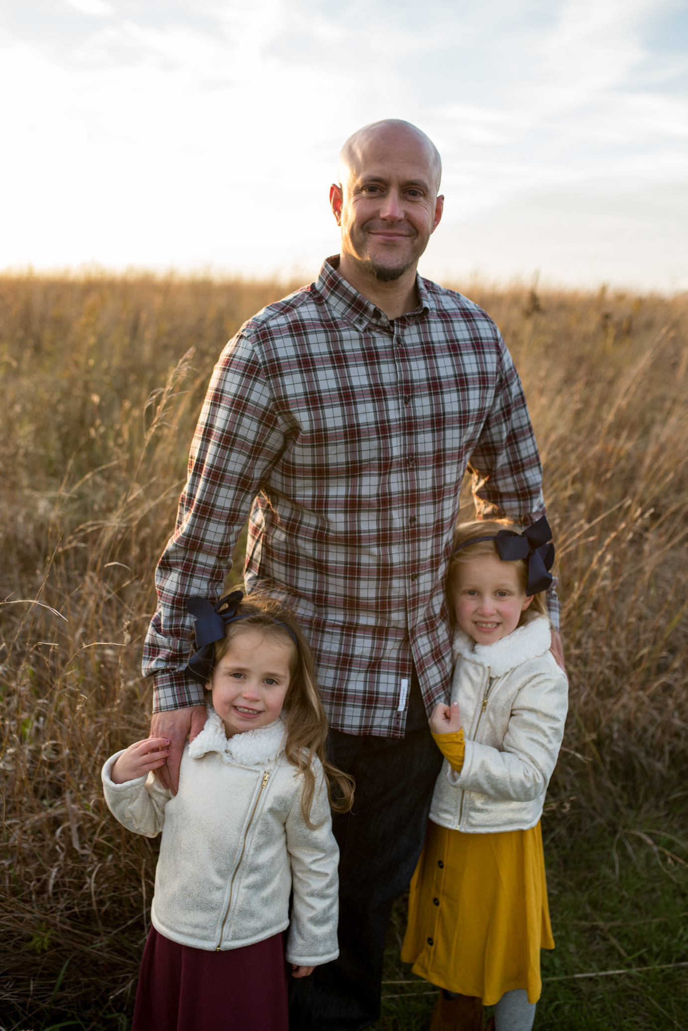 Dad posing and smiling with arms around his two daughters during a Waukesha Photography session