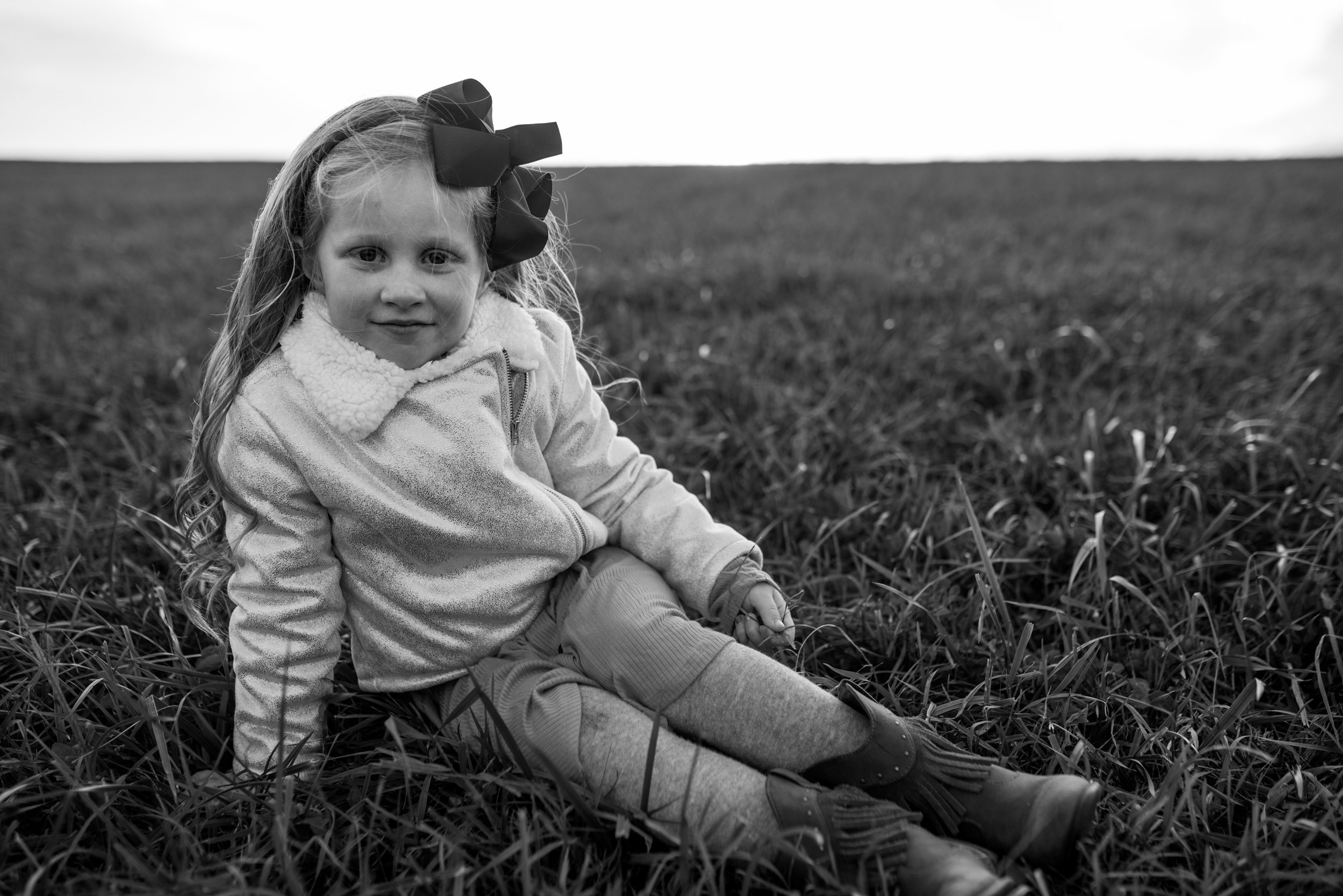 Young girl sitting in a field smiling