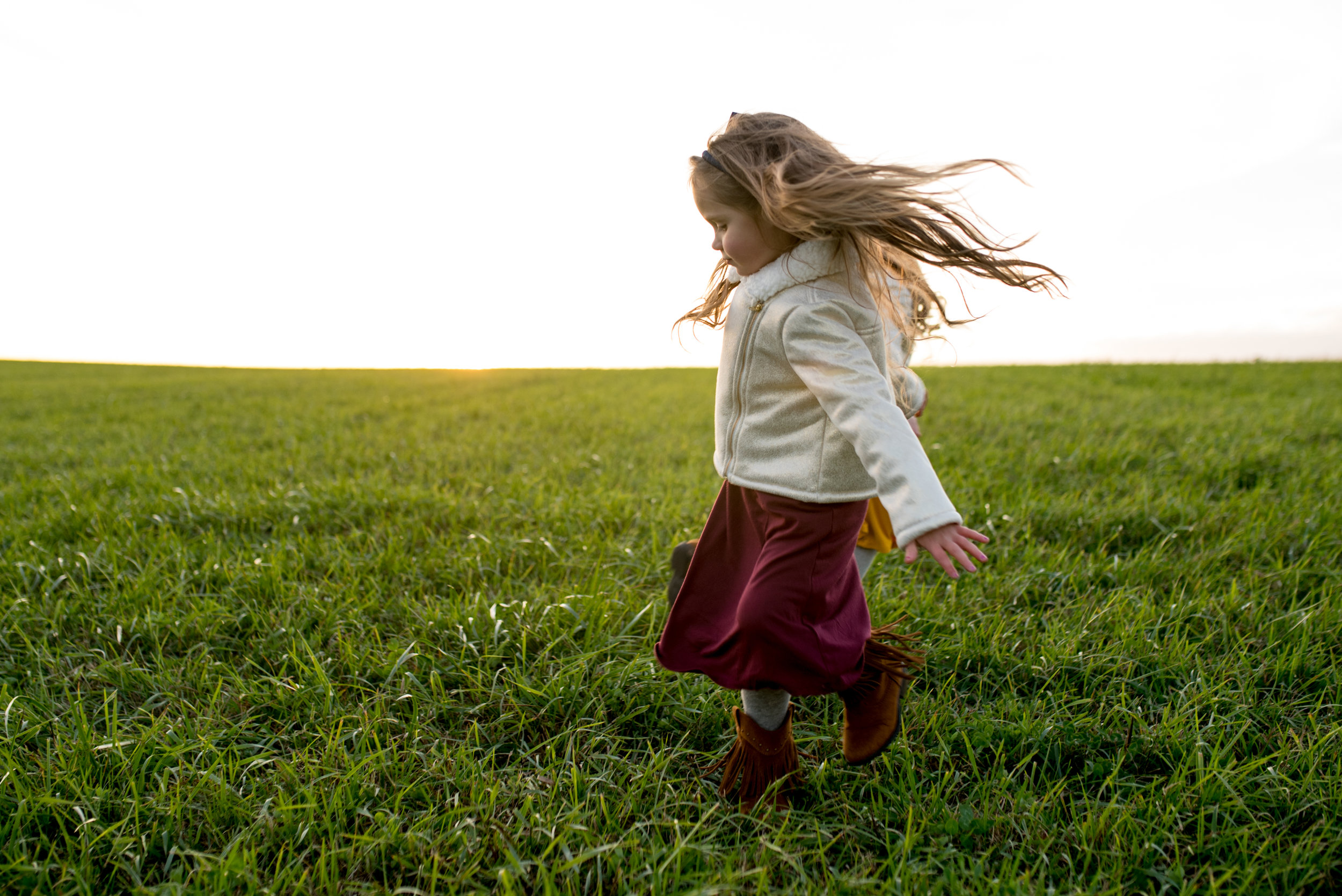 Young girl with long hair and a dress on twirling in a field