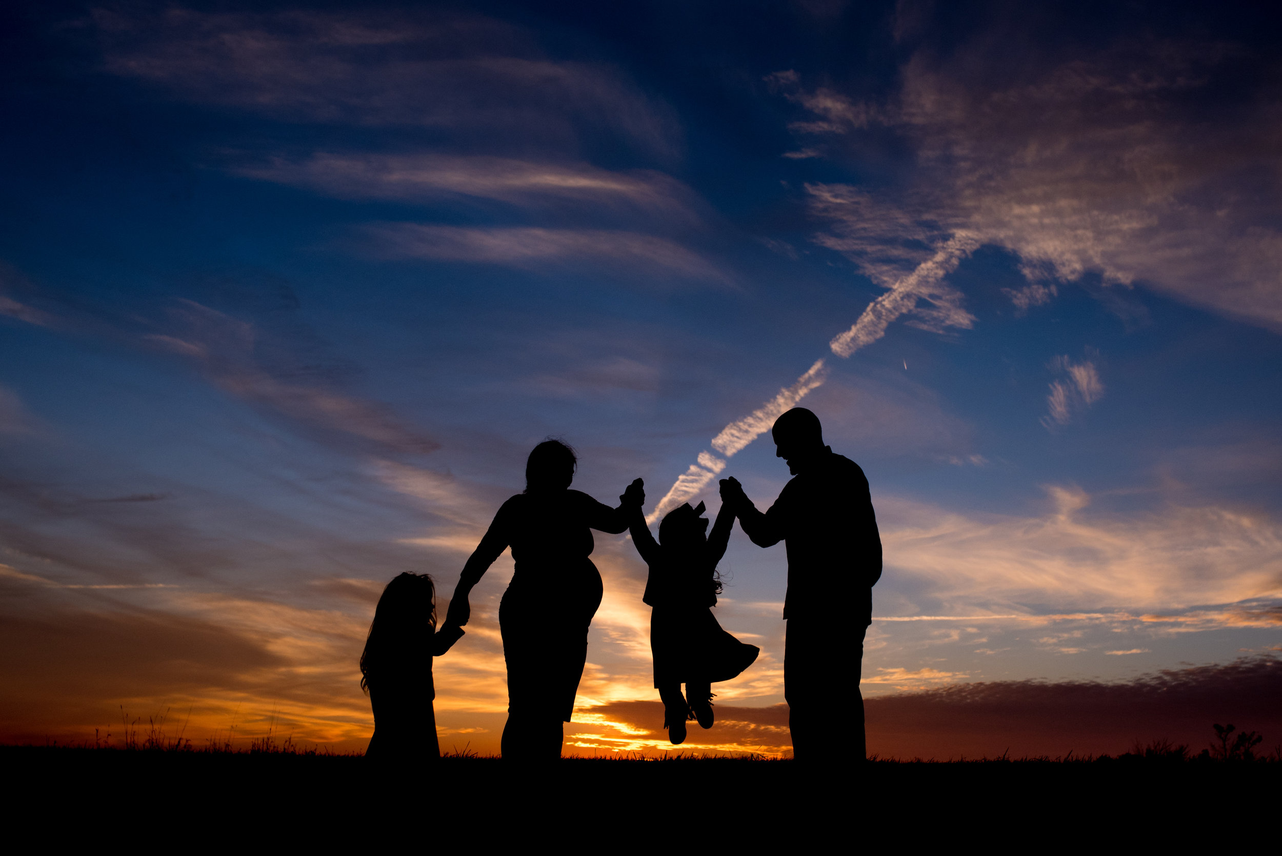 Silhouette of a family at sunset swinging one of their daughters by hand