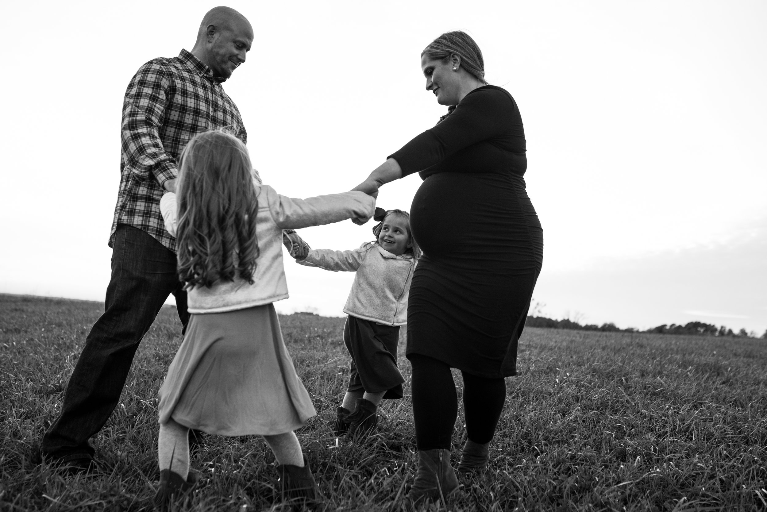 Family of four playing ring around the rosy, daughter smiling at dad, pregnant mom