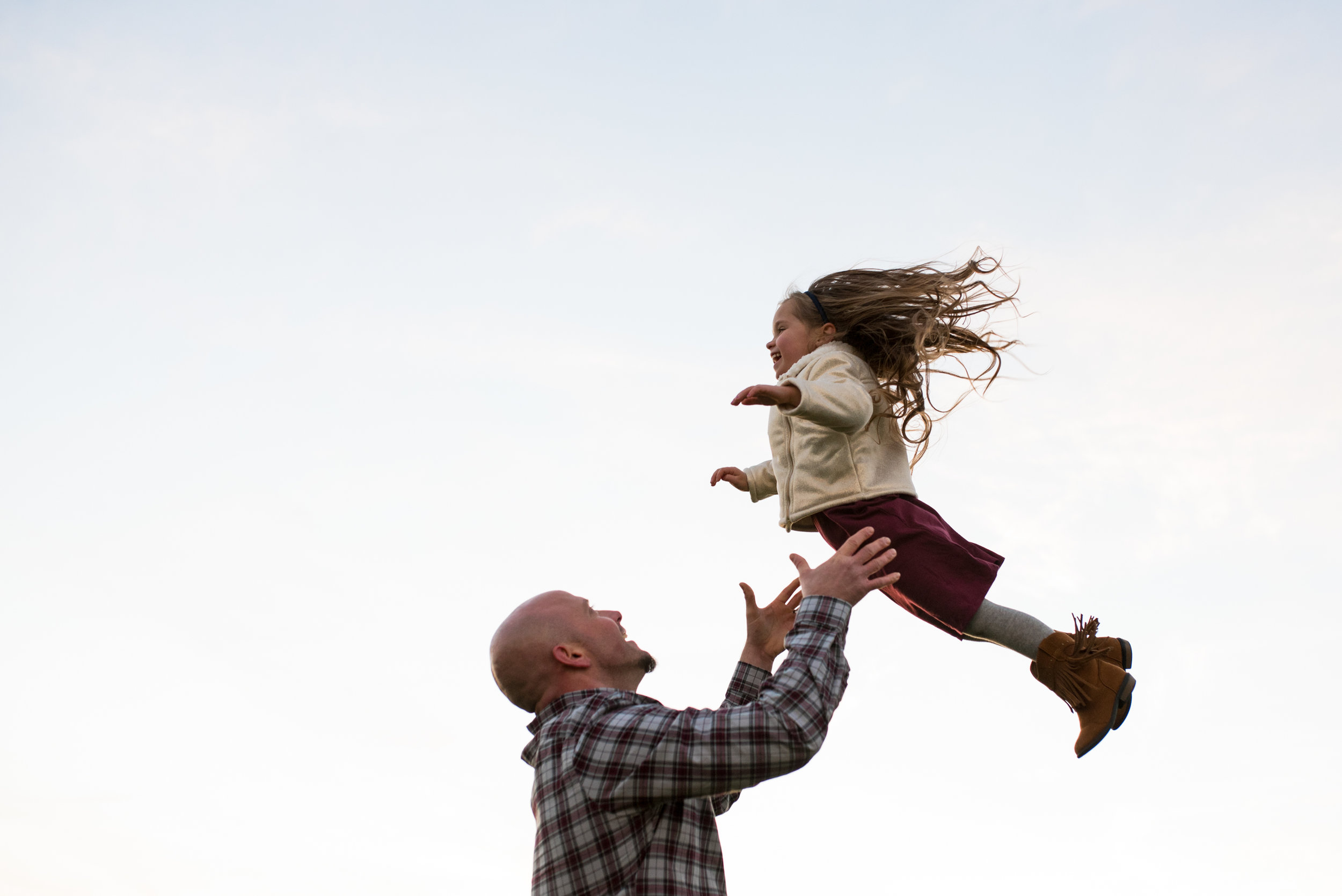 Dad throwing daughter in the air and about to catch her
