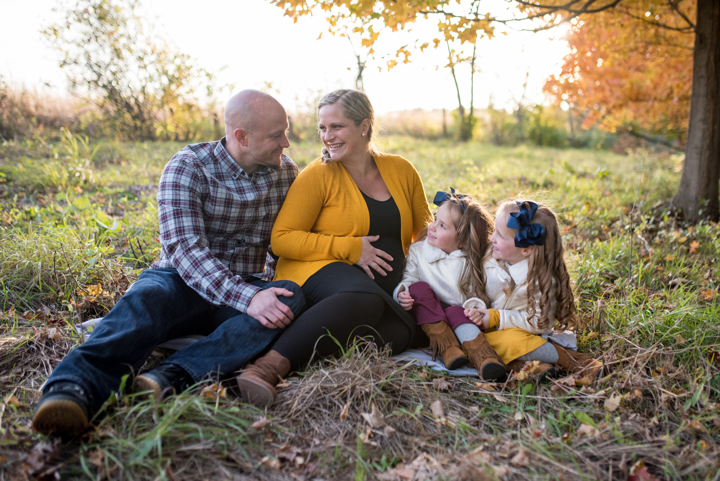 Family of four sitting on the ground in a field, pregnant mom and daughters smiling at dad