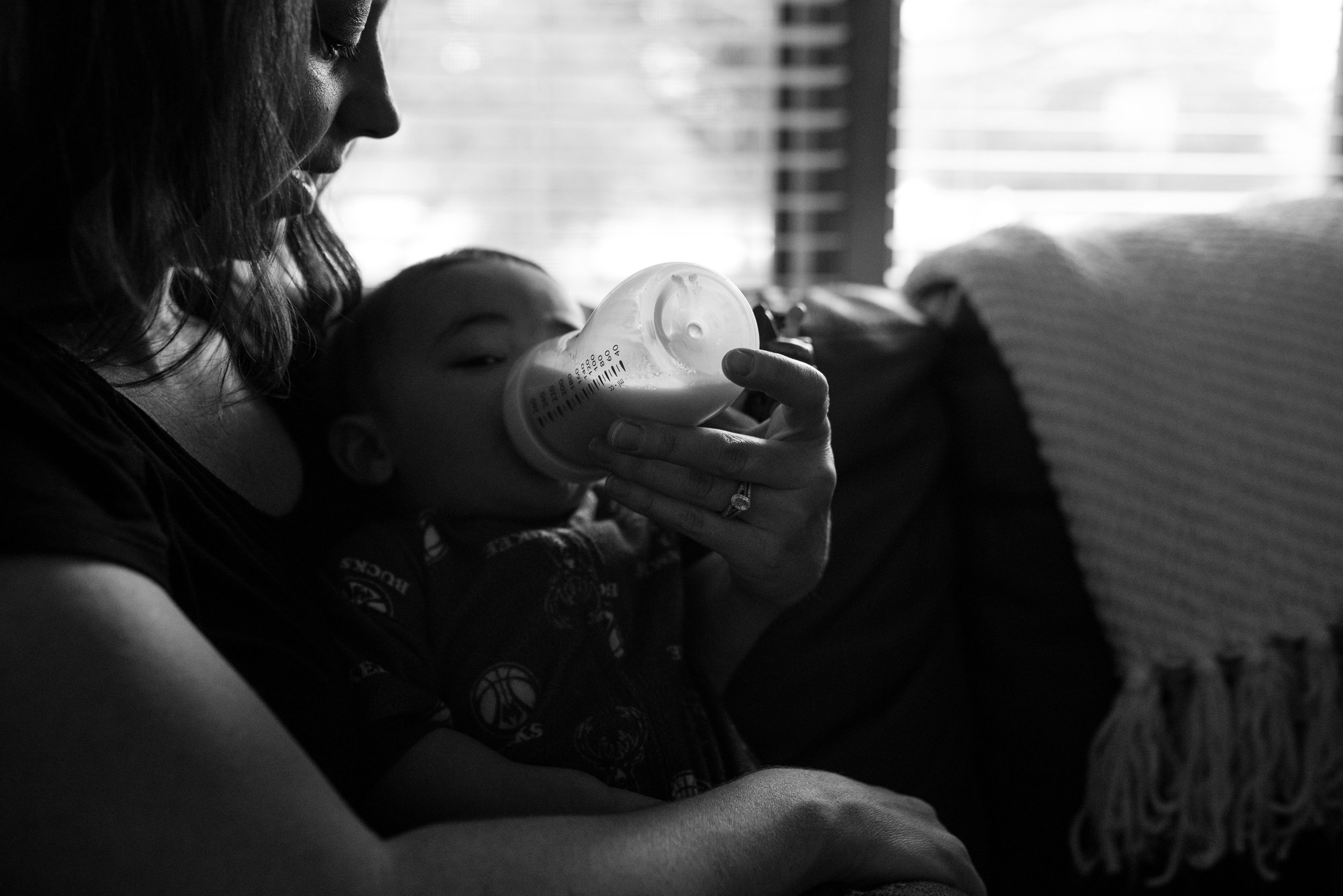 Mom Feeding son a bottle sitting on the couch during Muskego Family Photography session