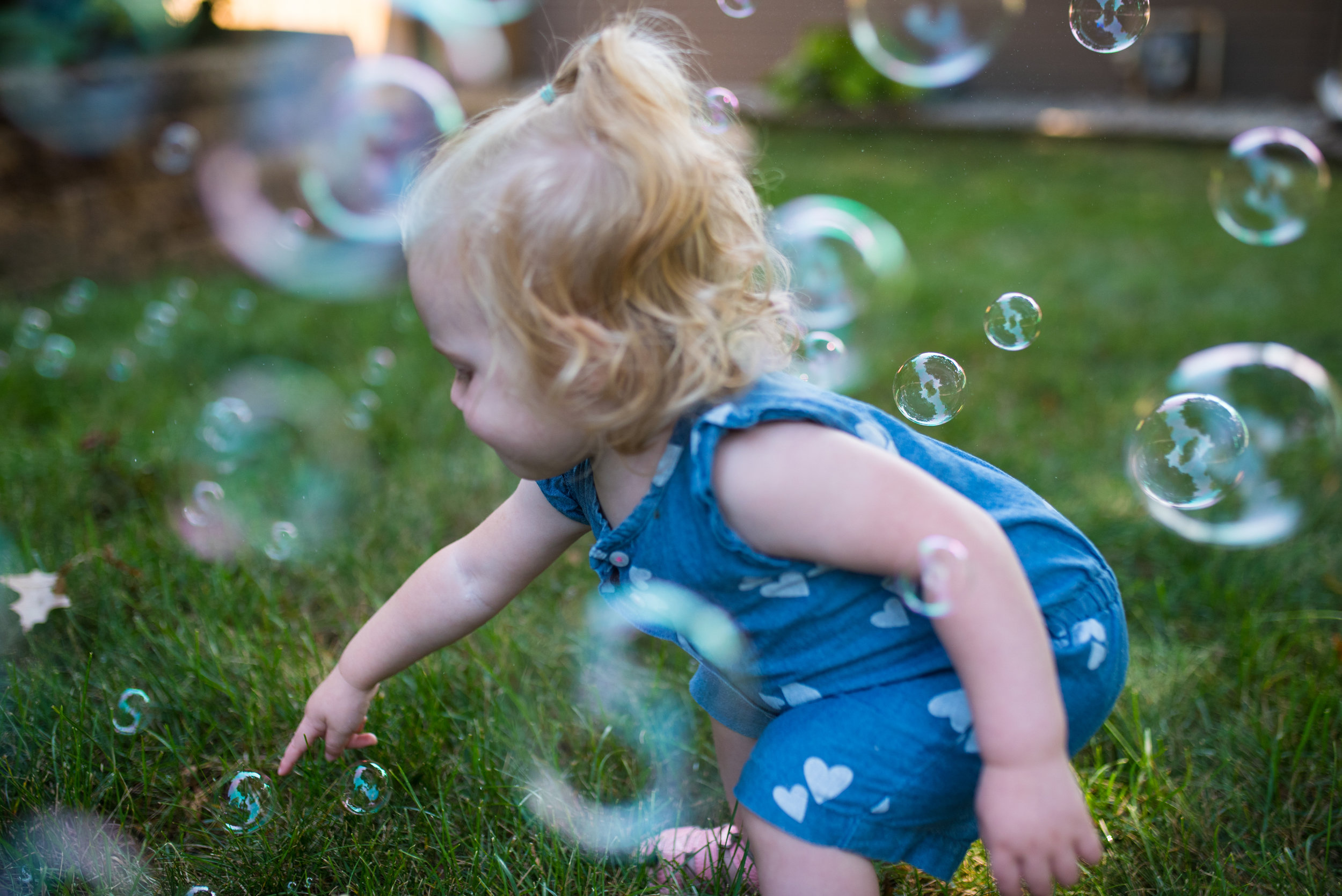 Toddler girl trying to poke bubbles in the grass