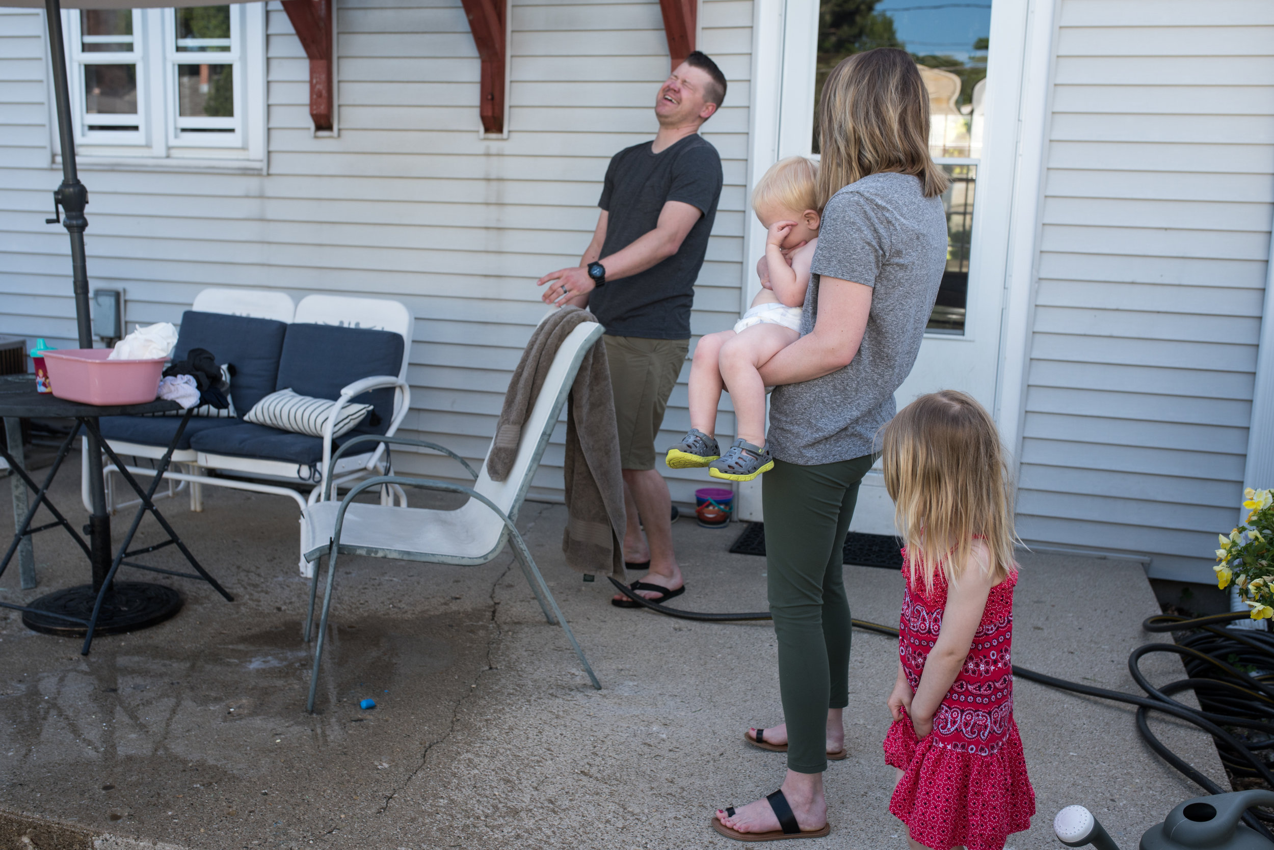Dad laughing while spraying off patio with a hose, mom, son and daughter look on
