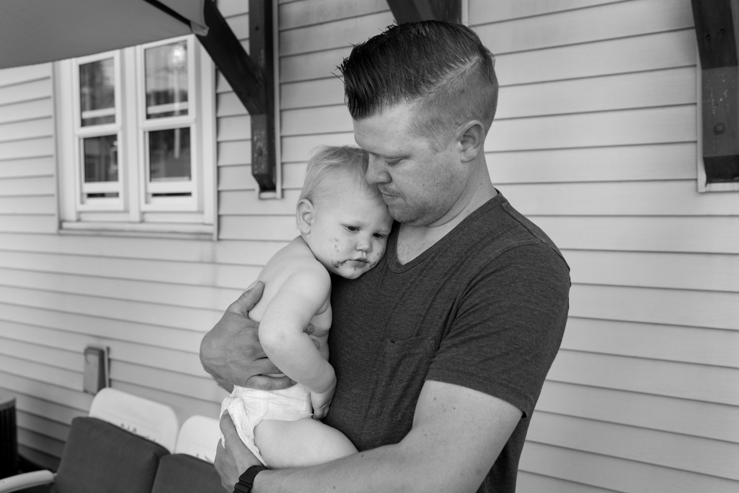 Dad holding young son against his chest during Wauwatosa Photography Session