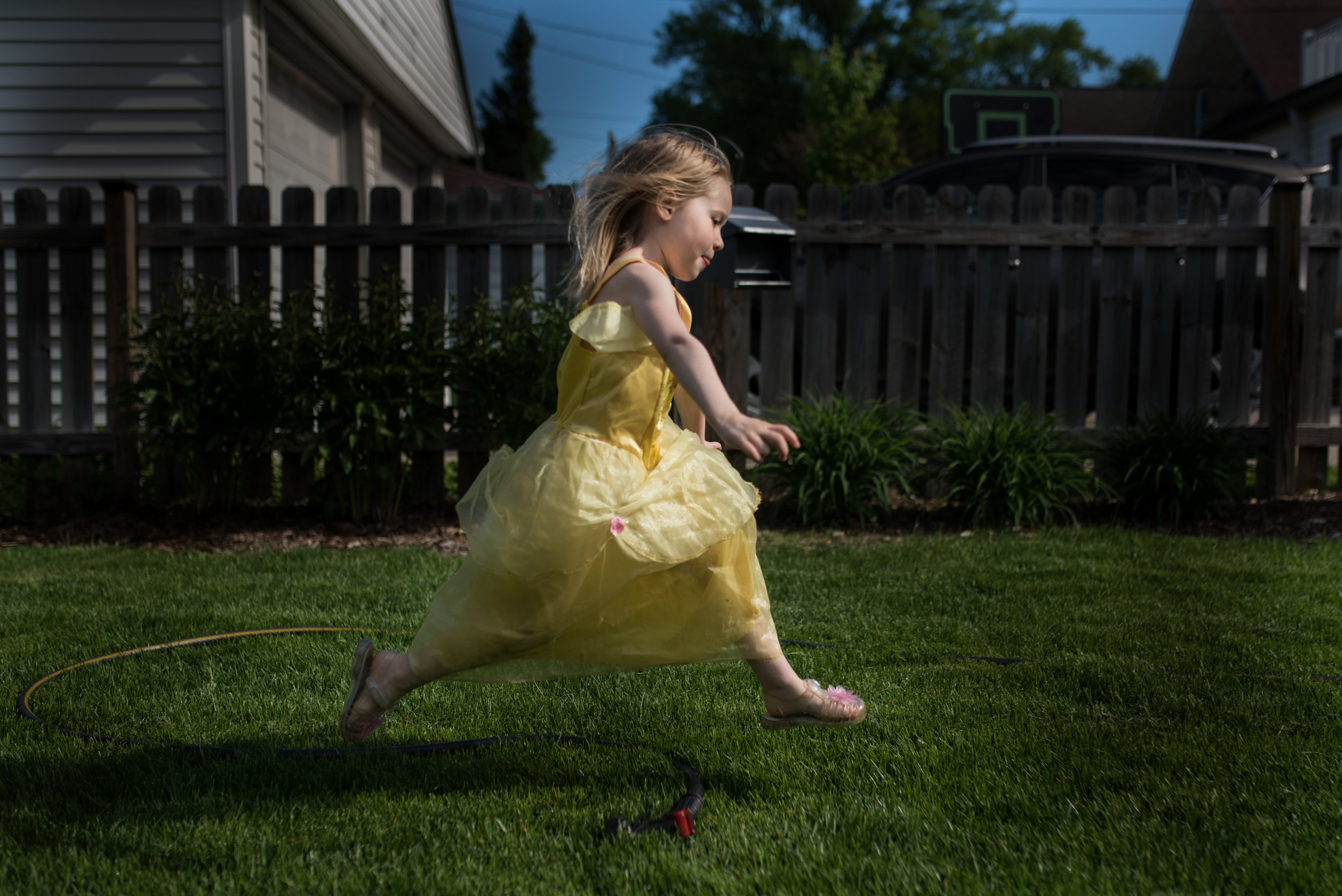 Young girl running and jumping in yard wearing a princess dress