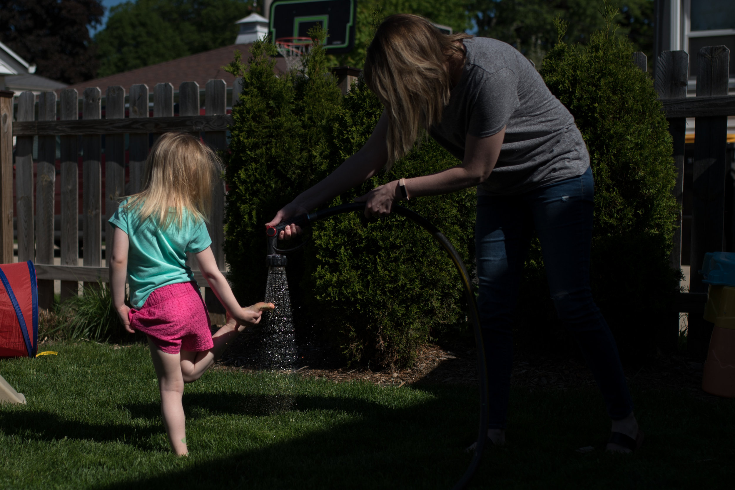 Daughter getting grassy feet sprayed off by hose in yard during Wauwatosa Photography session