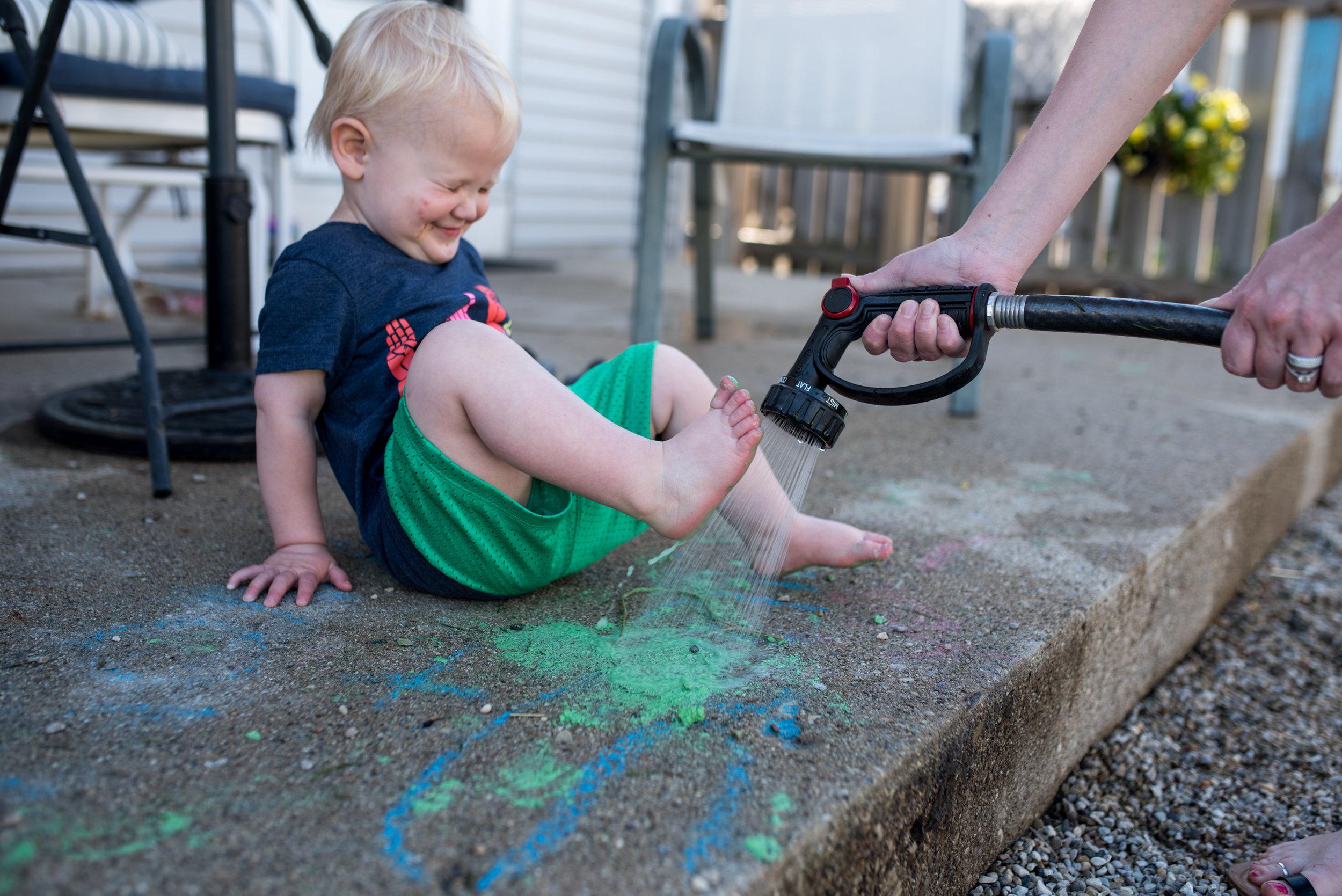 Son getting grassy feet sprayed off by hose