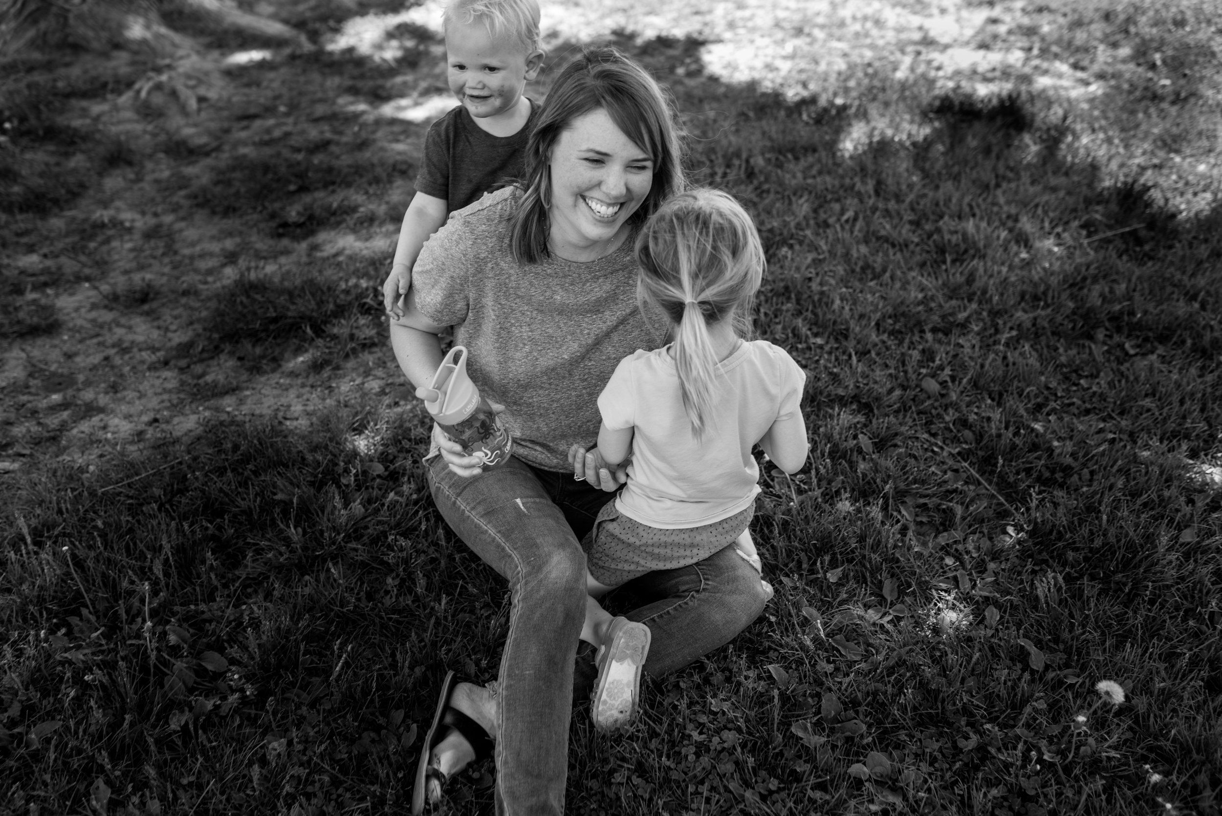 Son and daughter hugging mom while sitting in the grass, mom laughing