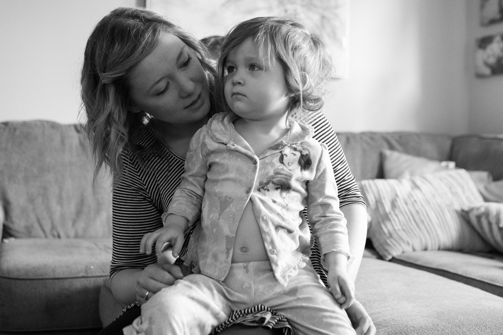 Mom holding daughter on lap, daughter in pajamas