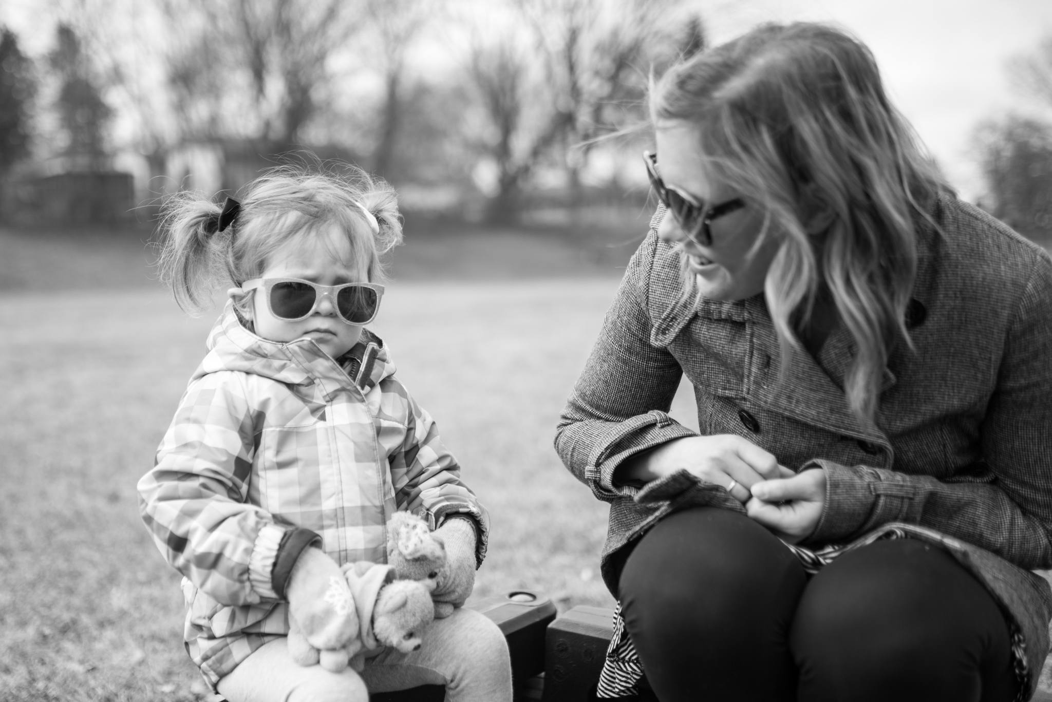 Mom smiling at young daughter while sitting at a park during a Greendale Photography session