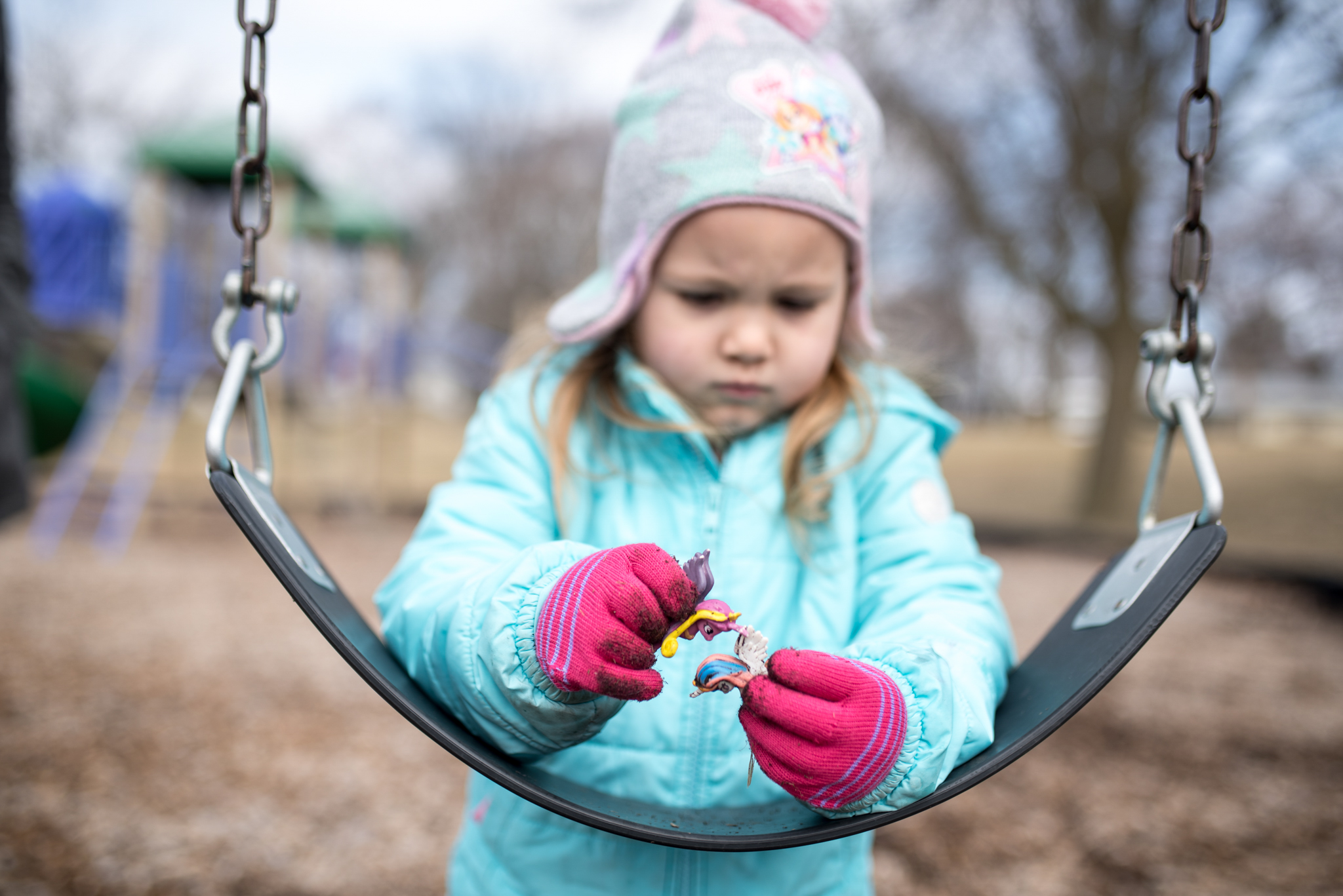 Young girl playing with pony toys on a swing at a park