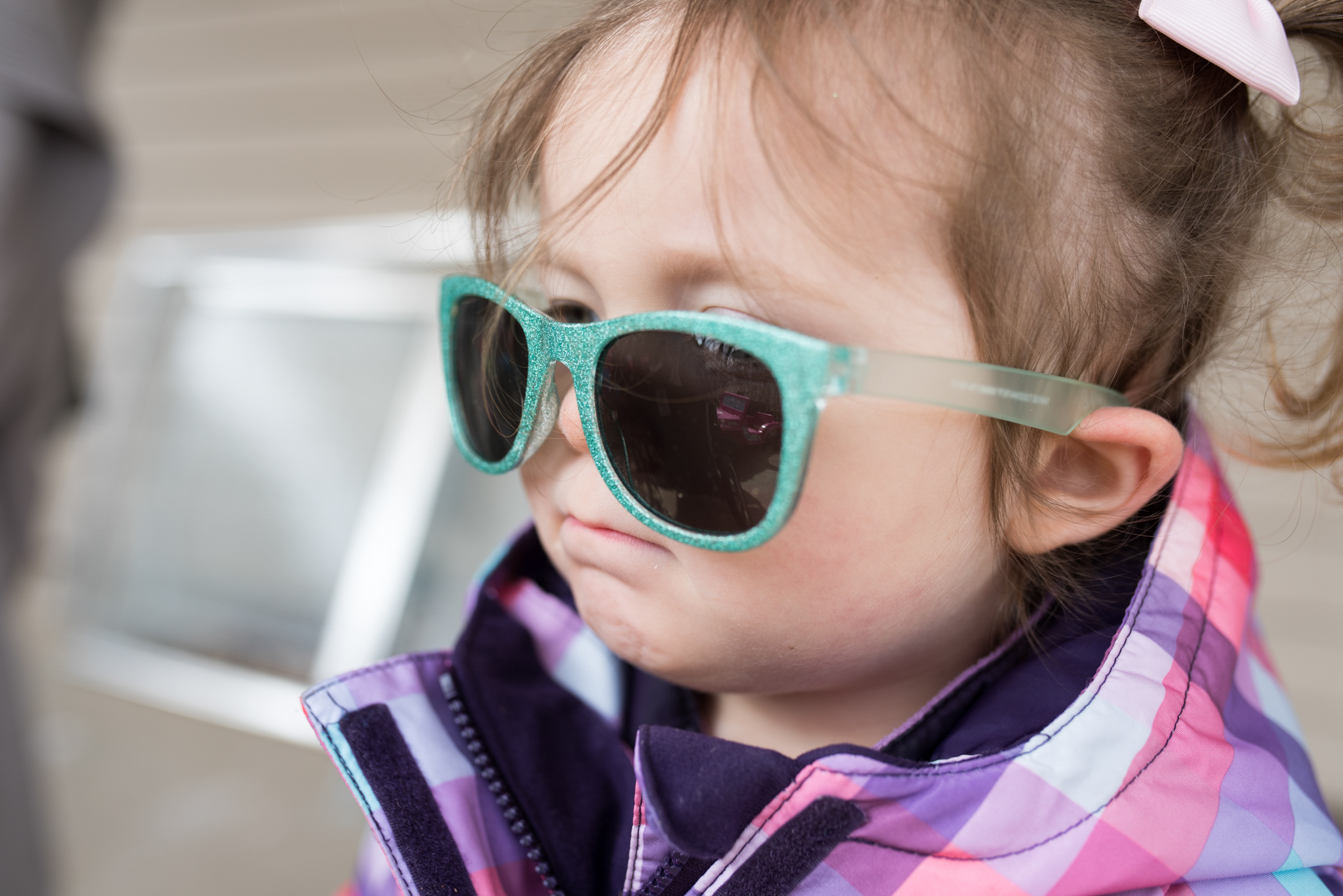 Young girl wearing pig tails and blue sunglasses